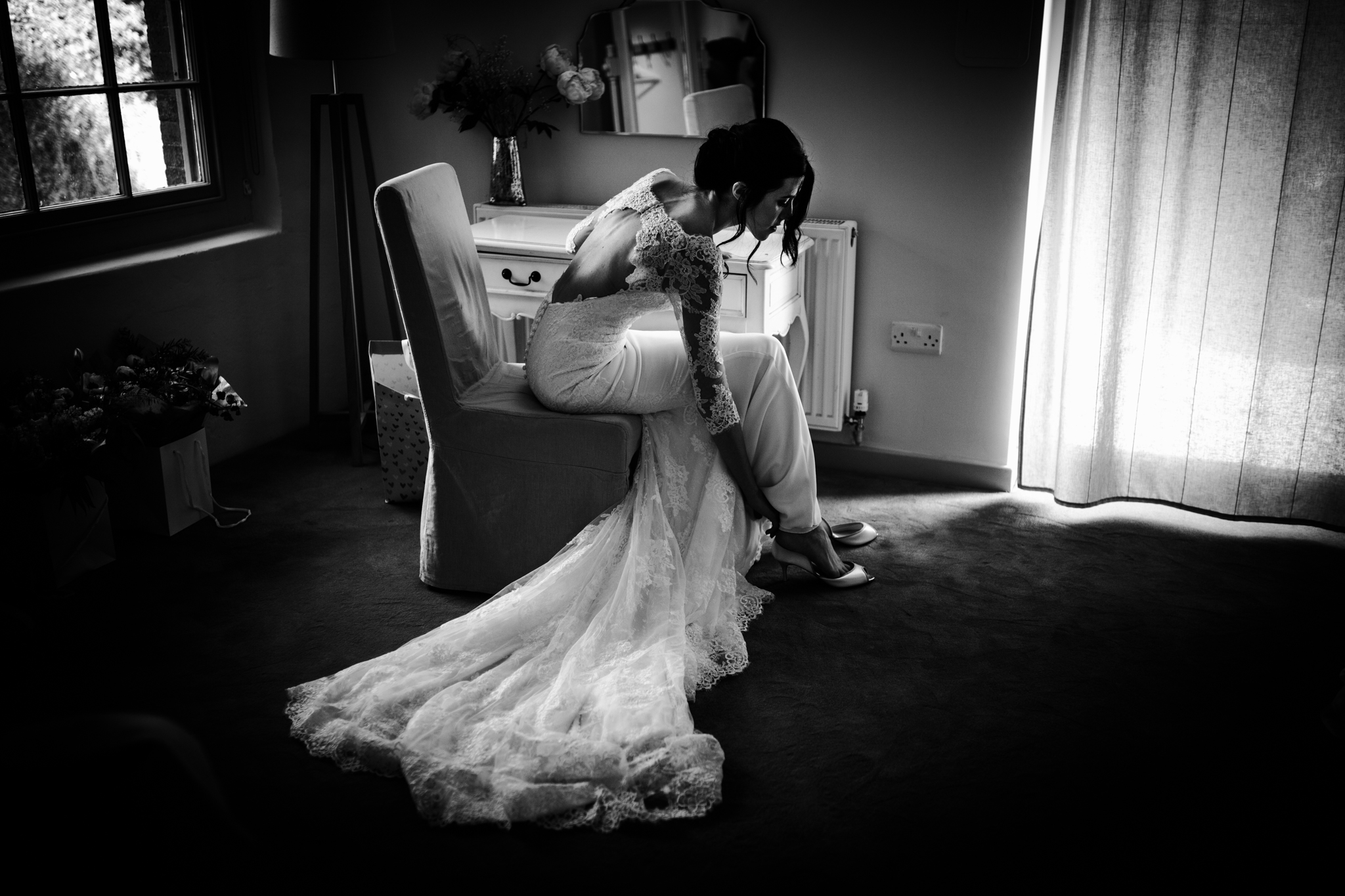 Bride putting her shoes on in a tidy hotel room