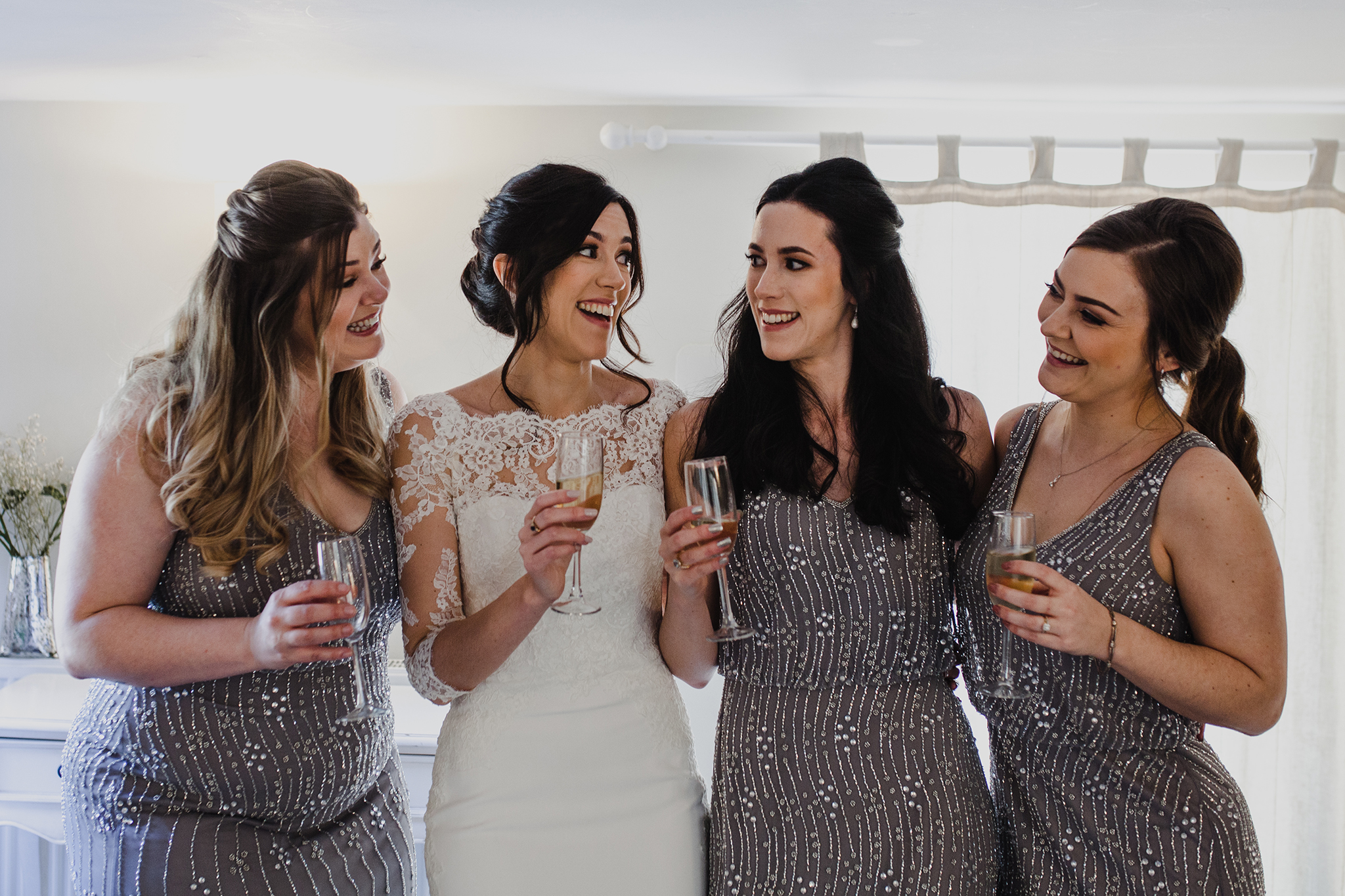 Bride and bridesmaids toasting and being happy in a hotel room