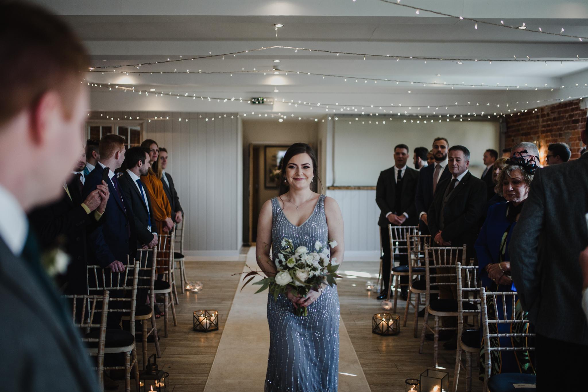 Bridesmaid walking down the aisle at Sopley Mill wedding venue