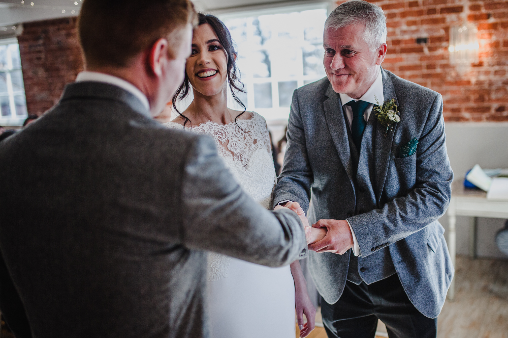 Father of the bride handing his daughter to her future husband