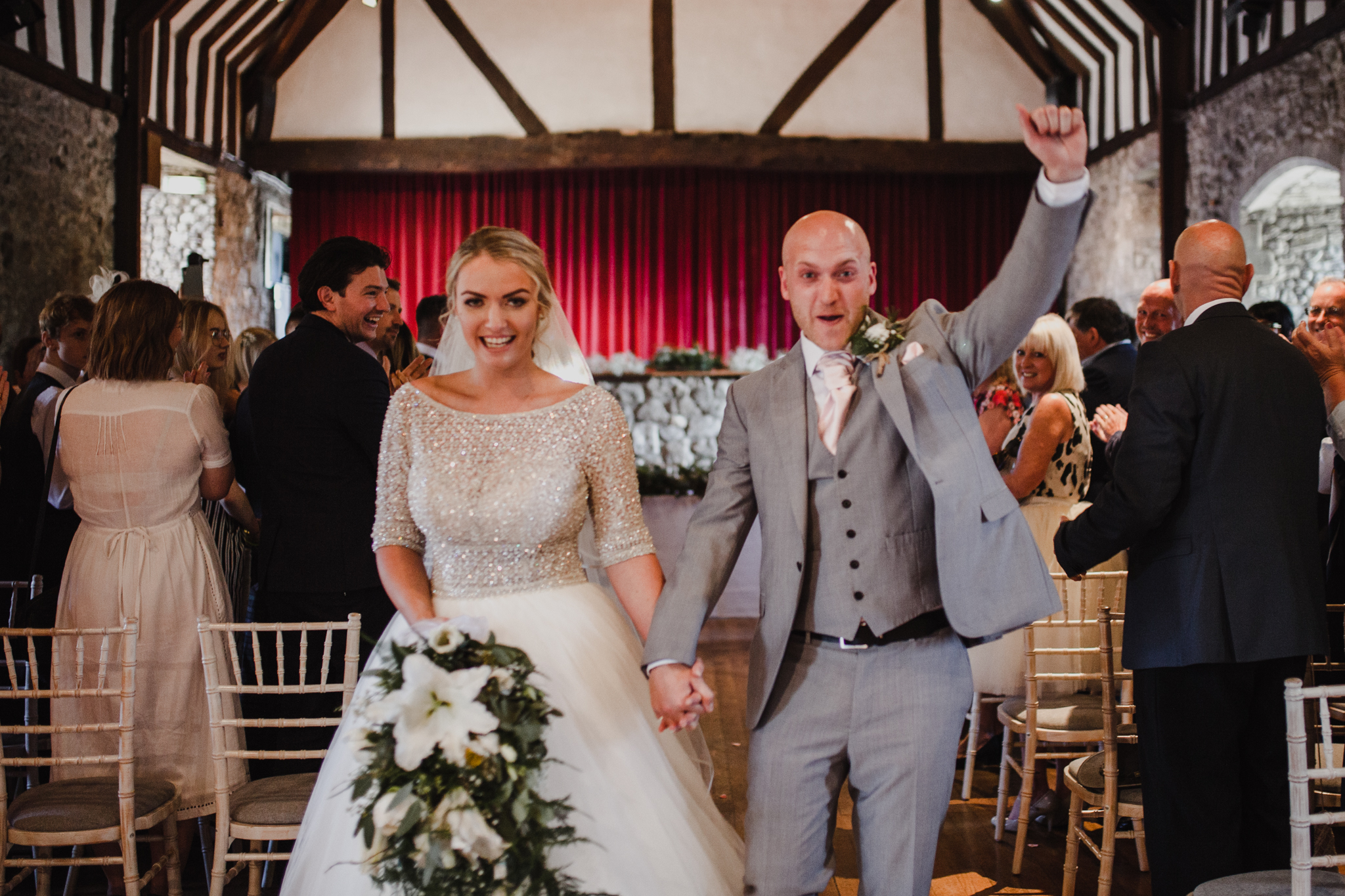 Very happy bride and groom celebrating as they walk down the aisle together