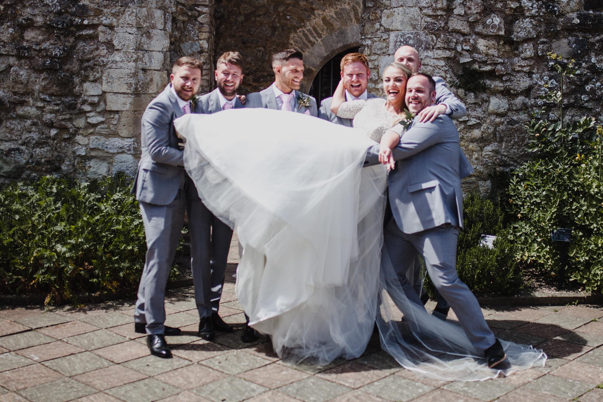 Groomsmen lifting up the bride in outdoor venue