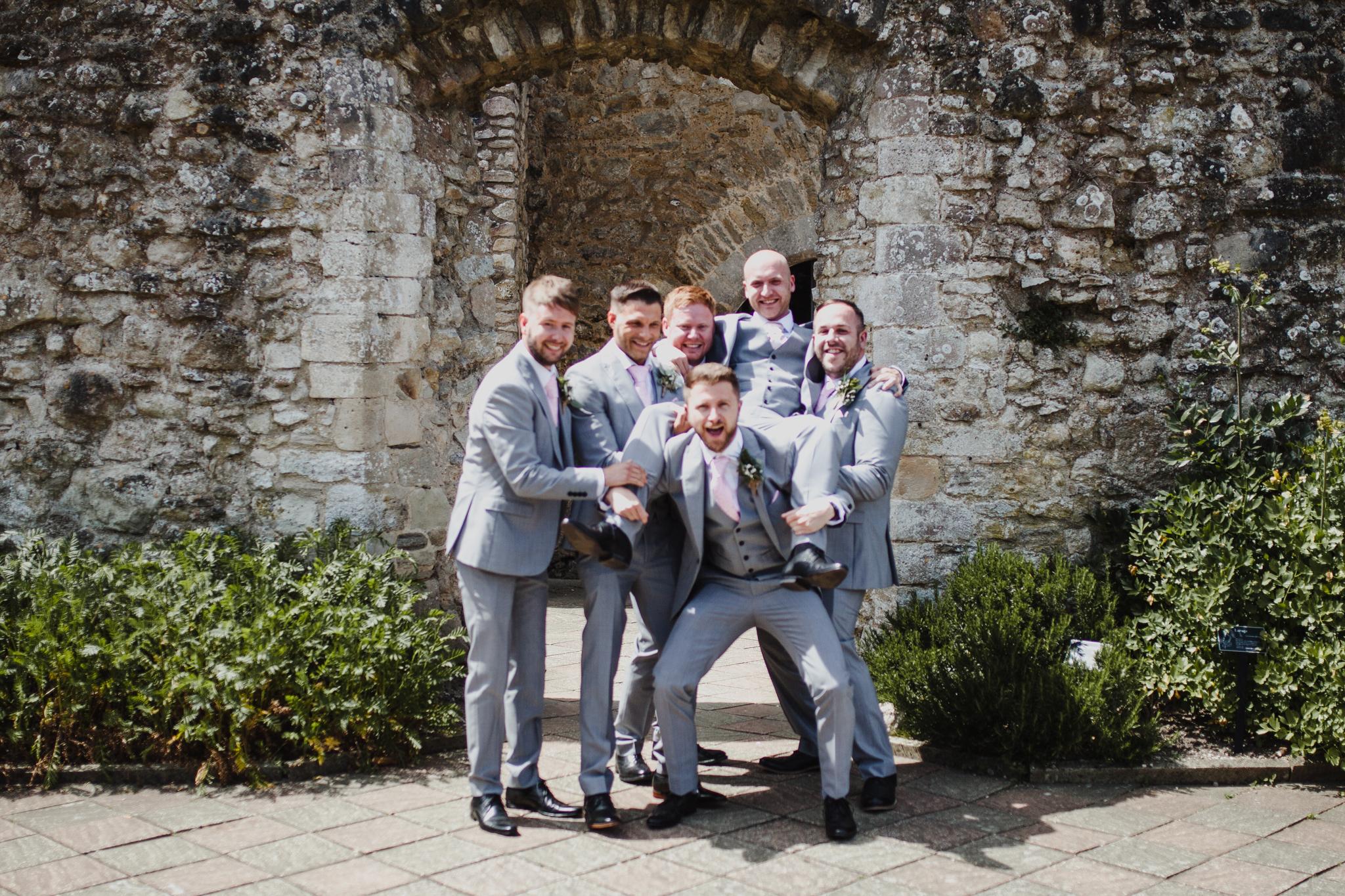 Groomsmen lifting up groom and celebrating