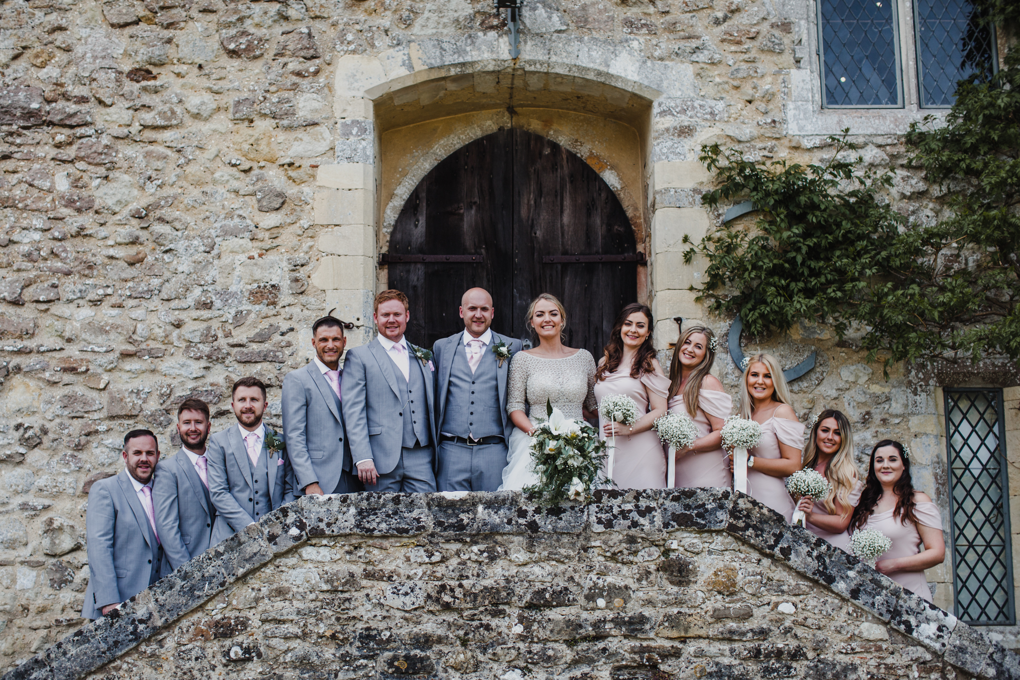 Bridal party lined up smiling in front of stone wall venue on stairs