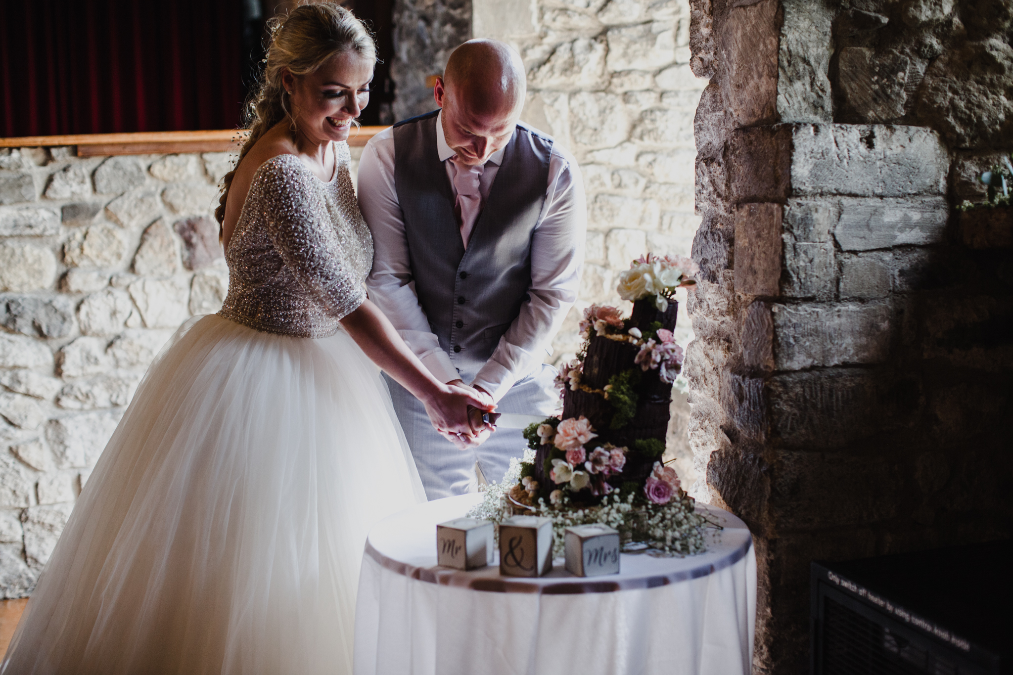 bride and groom cutting cake in window light