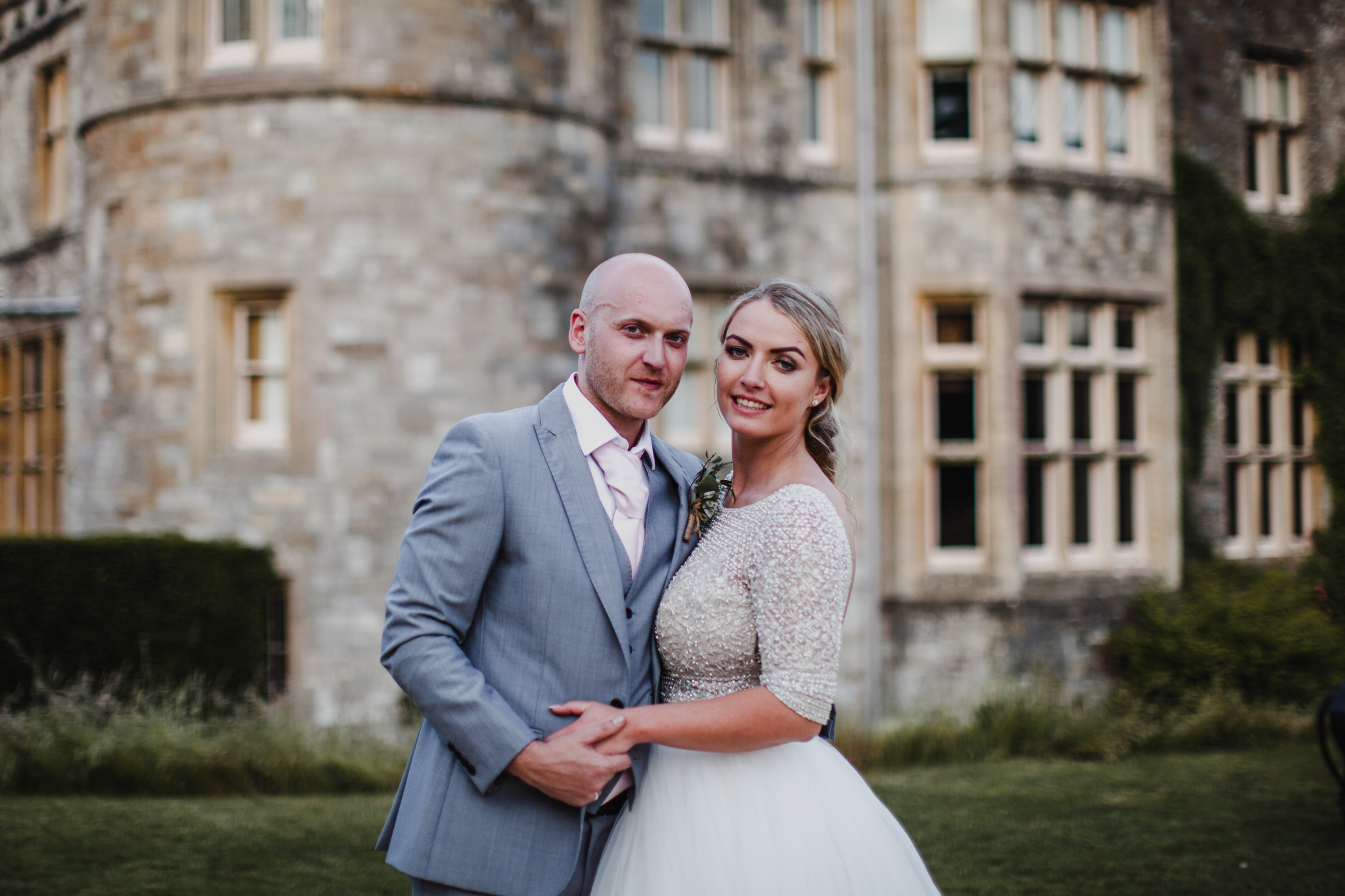 Bride and groom smiling in front of a castle