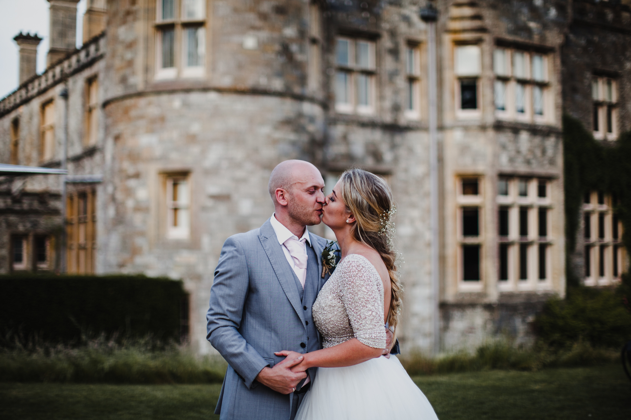 Bride and groom kissing in front of a stone english castle