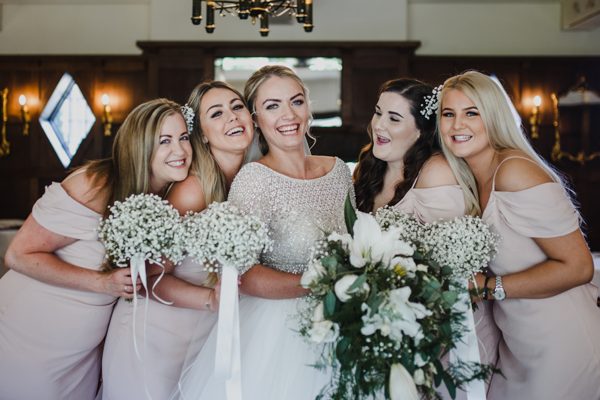 bride and her bridesmaids laughing together before a wedding