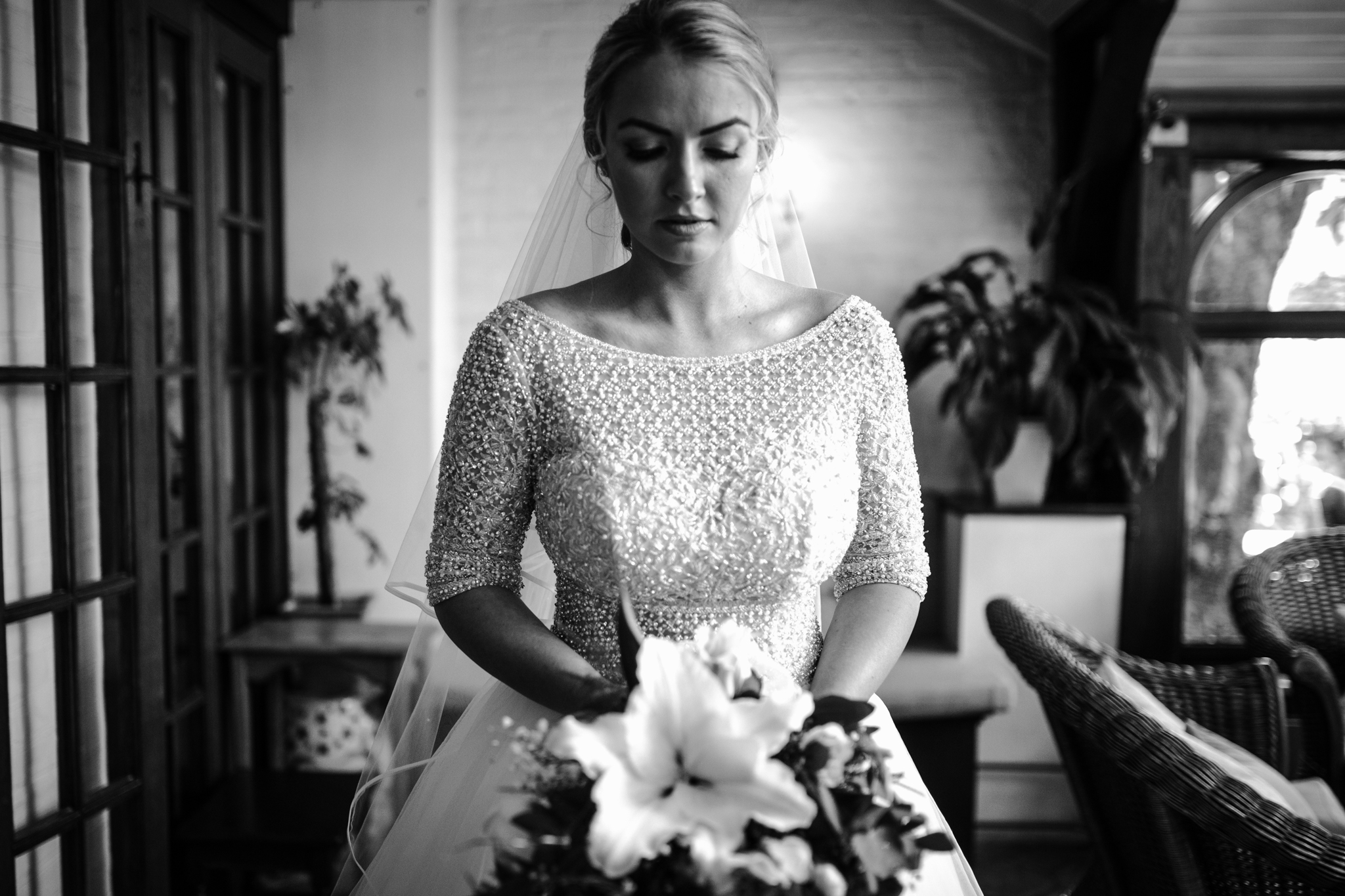 A black and white portrait of a bride and her flowers before the wedding