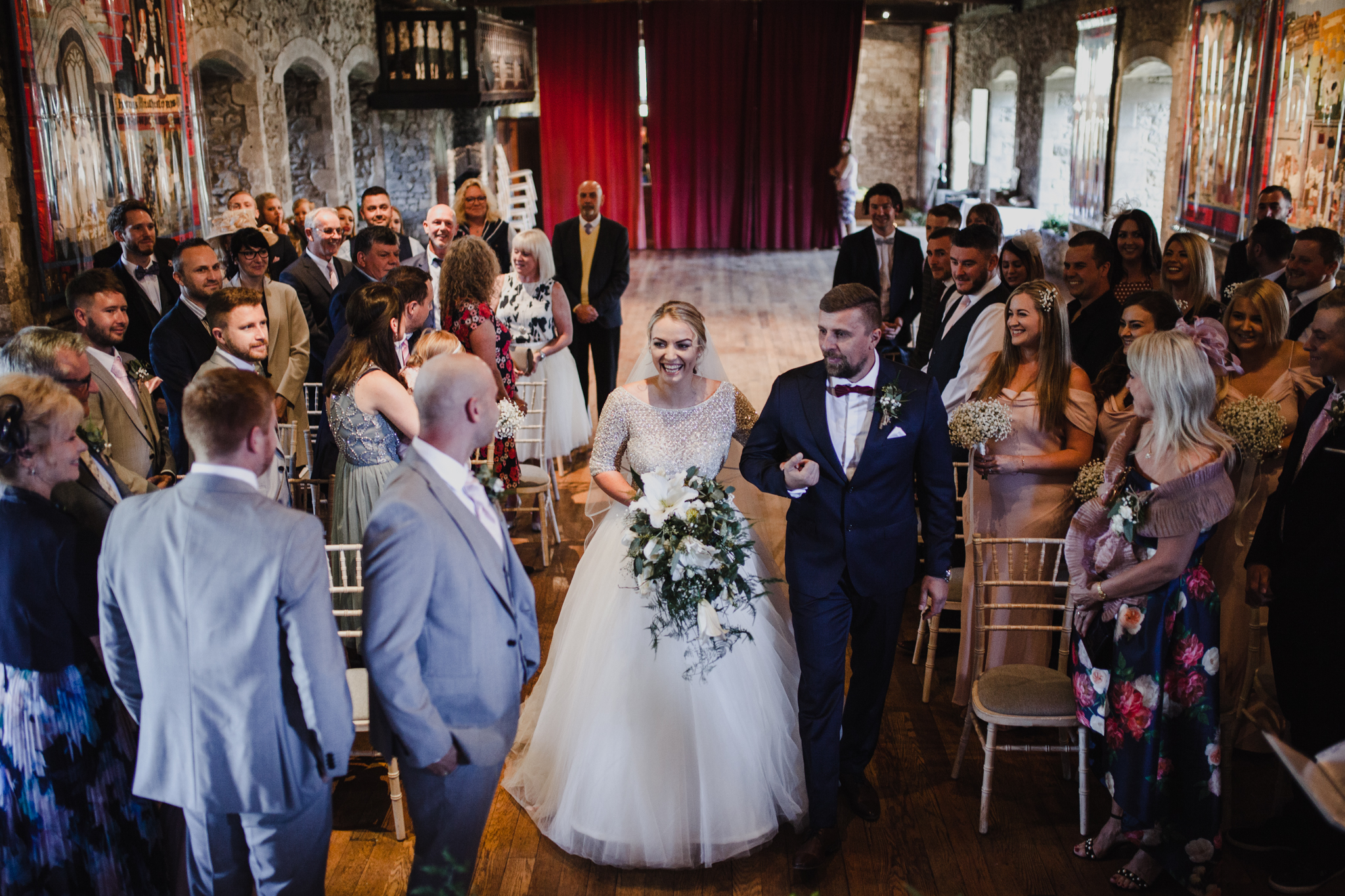 A bride and her father walking down the aisle in a dark castle style venue