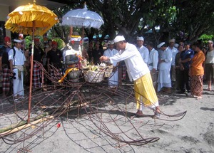 Pak Prana blesses the Coral Goddess in a Balinese ceremony before she is carried to rest under the sea