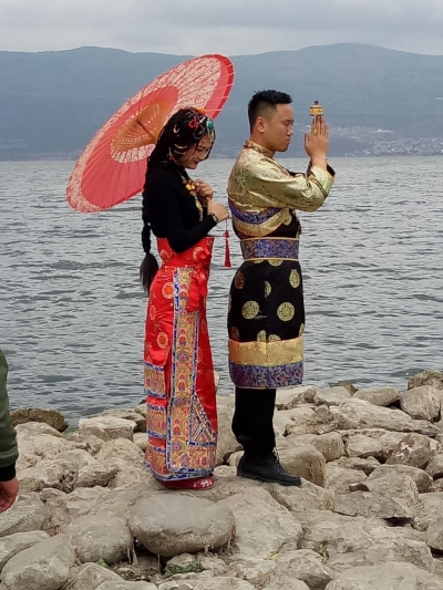 A bride and groom in traditional bridal costume at Dali Lake