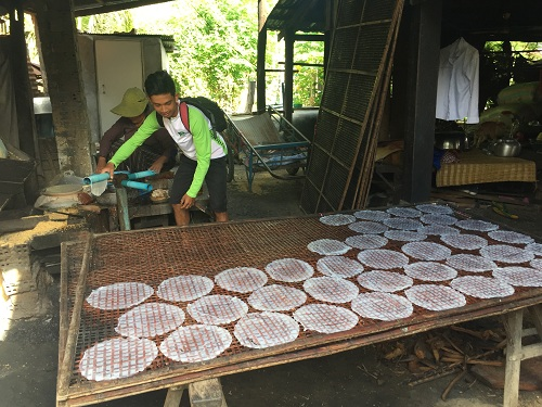 Pum helps explain traditional methods of making rice paper in a local village. Courtesy M. Wyse