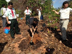 MOS Desmond Lee plants a Pteleocarpa lamponga that had been extinct in Singapore, with the help of Robert Teo, Dy Director of NParks (right) and scouts.