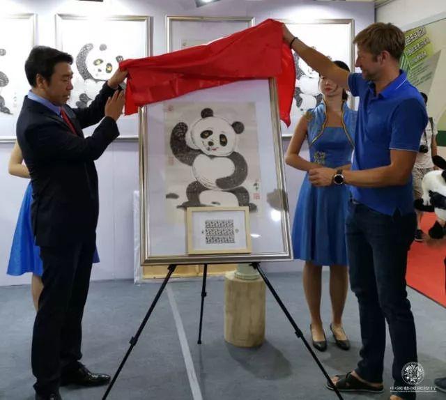 """刘中(左)与马尔代夫邮政官员为""""太极熊猫""""邮票揭幕"""