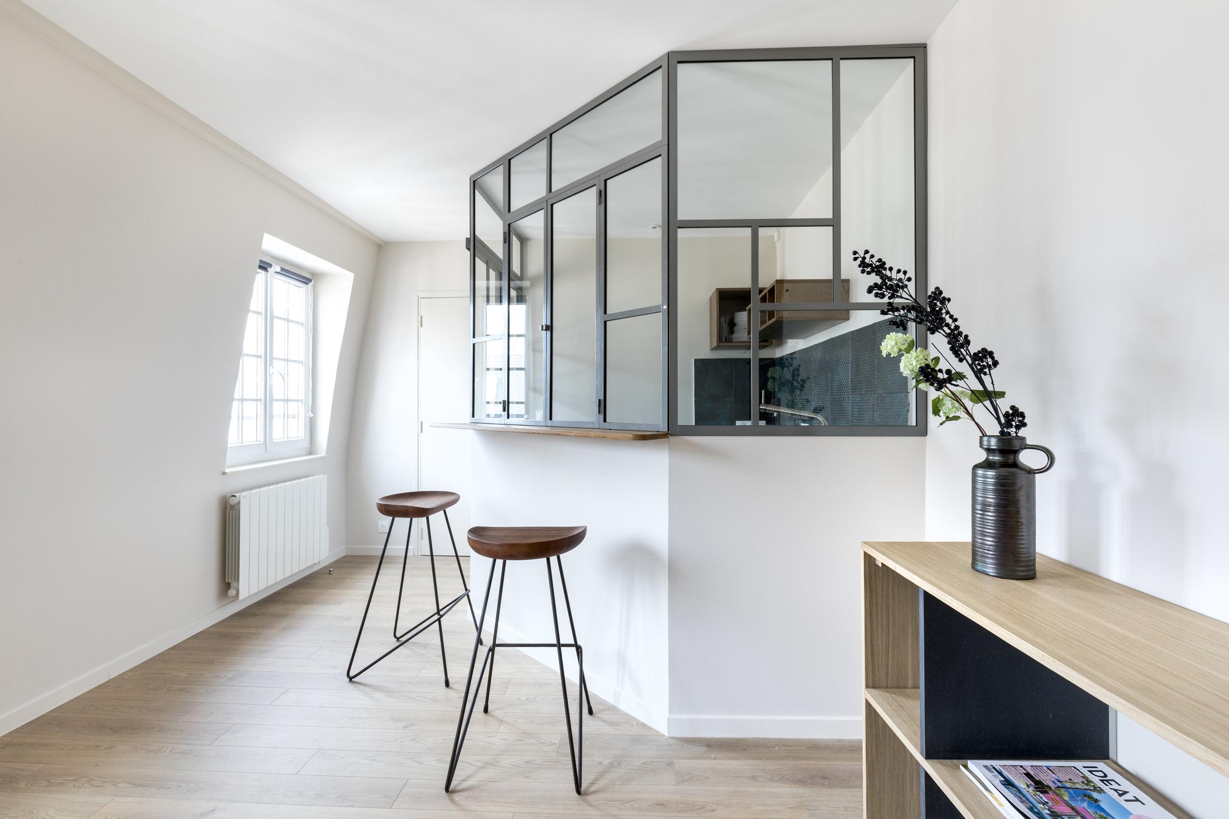 Verrière sur-mesure type atelier en métal avec ouvrants pour séparer la cuisine et le salon avec des assises en bois massif travaillées