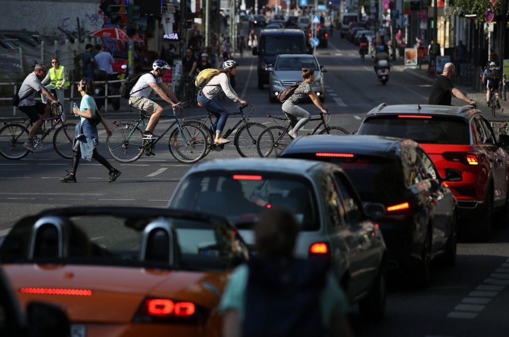 Alcuni ciclisti attraversano la strada mentre le auto aspettano al semaforo, Berlino, Germania – Sean Gallup/Getty Images