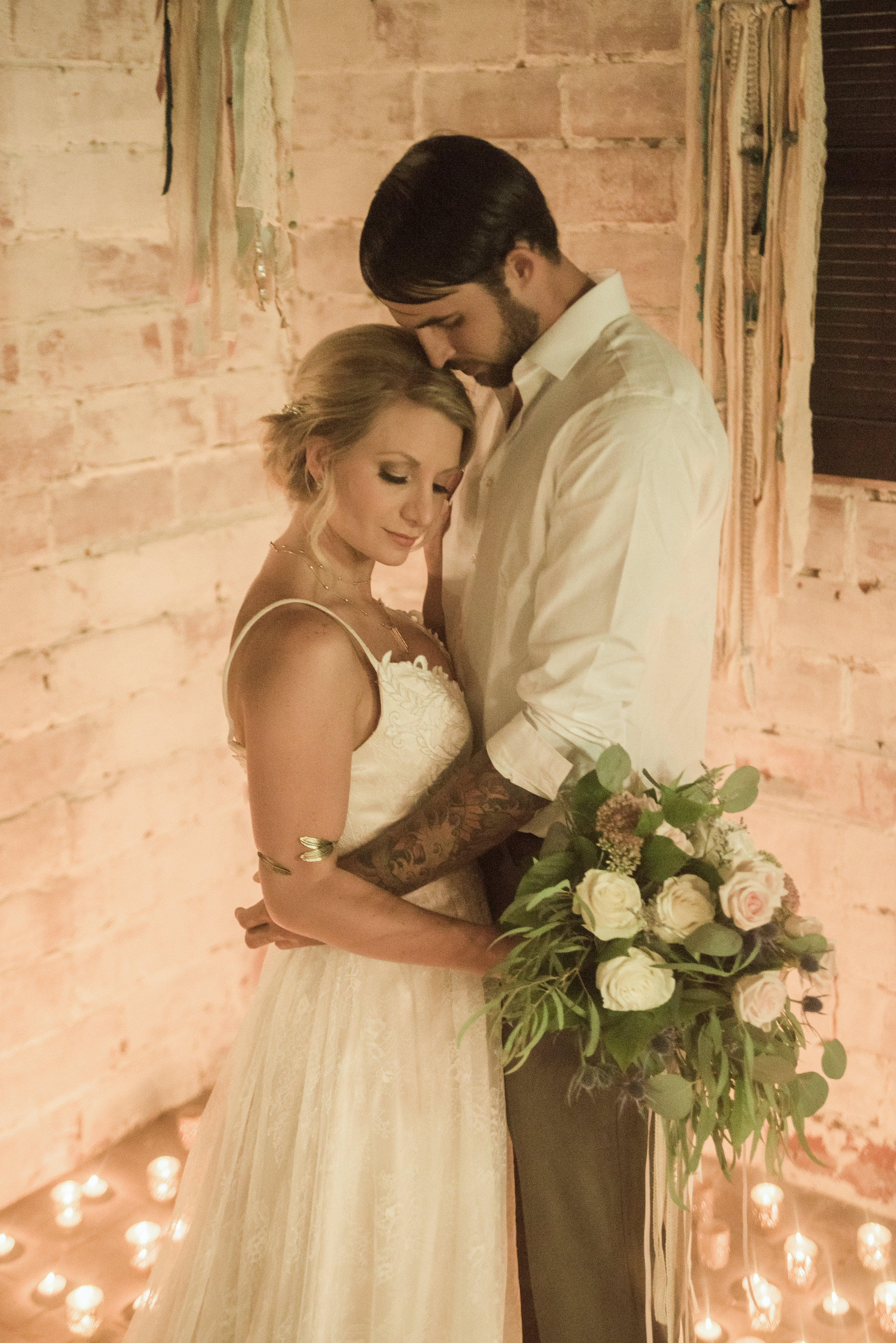 Models Nicole Oidtman and David Elkins pose bathed by candlelight in the stunning stable turned wedding venue.