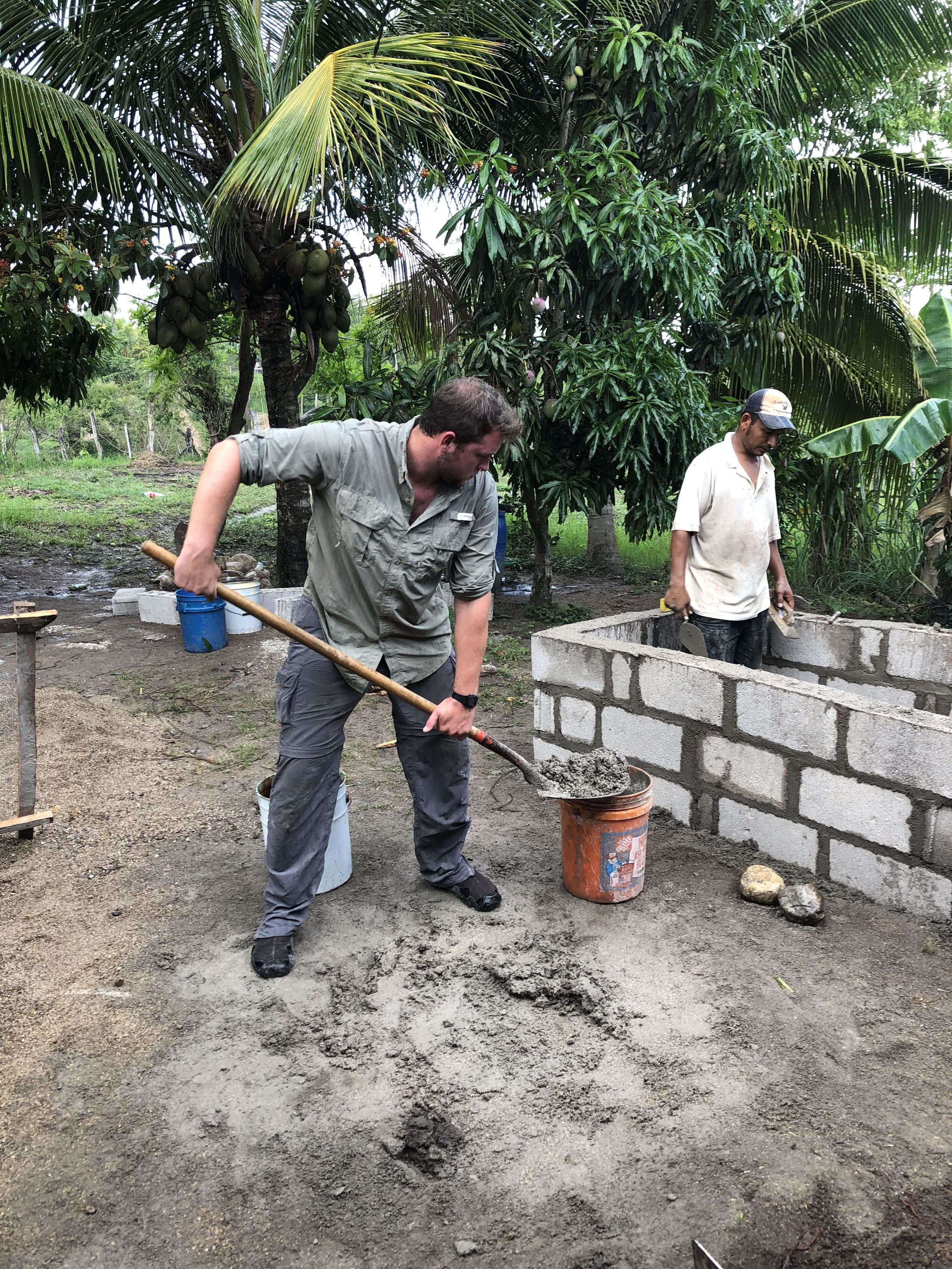 Corley mixes sand and concrete for latrine construction