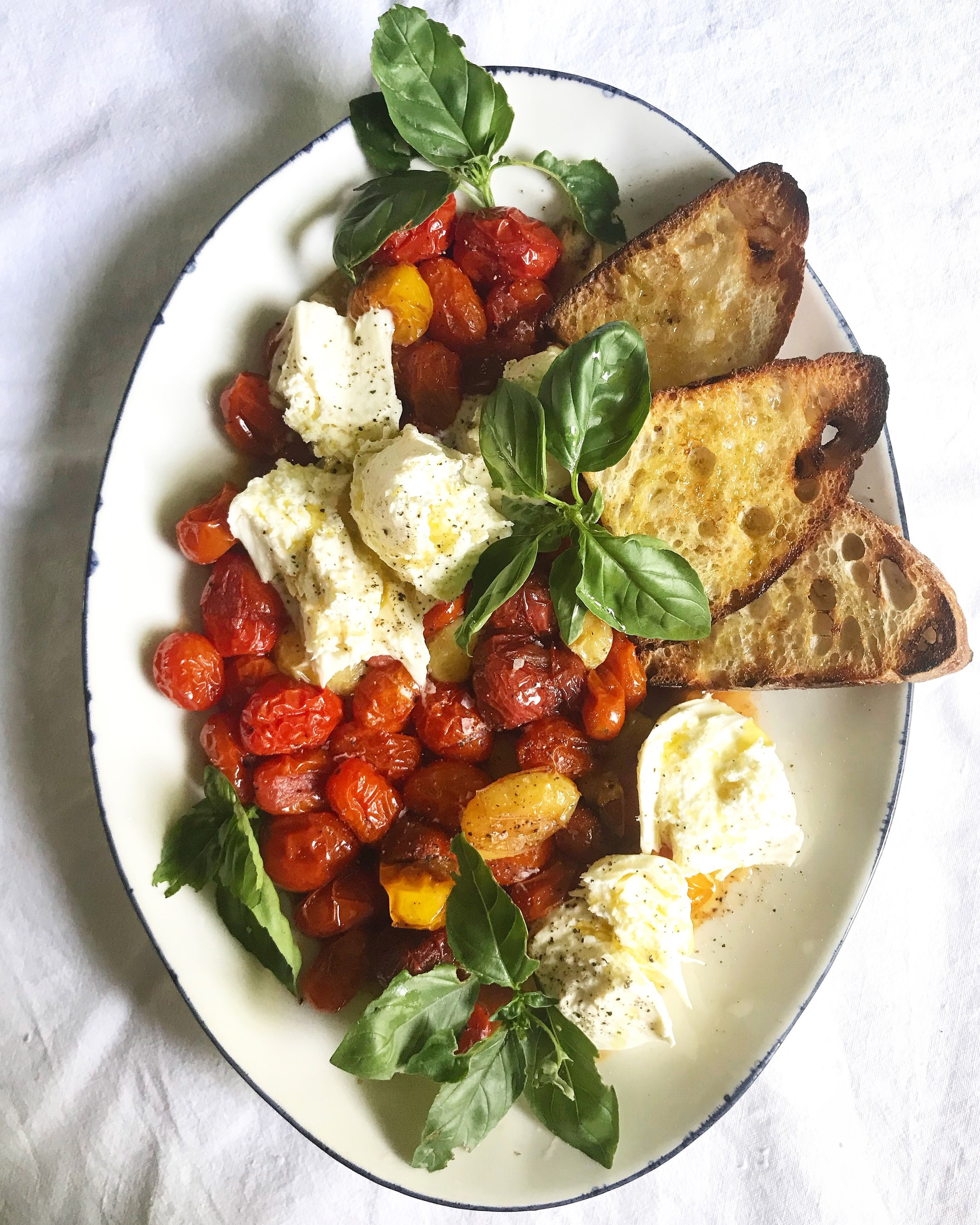 HERE IS WHAT YOU NEED: - 1 1/2 pounds (about) cherry tomatoes (I used multicoloured ones)3 - 4 garlic cloves (large), smashed4 tablespoons of extra virgin olive oilflaky sea saltfreshly ground pepper1 ball (250 g) fresh buffalo mozzarellarustic bread, slicedsea saltfreshly ground black pepper (if using)