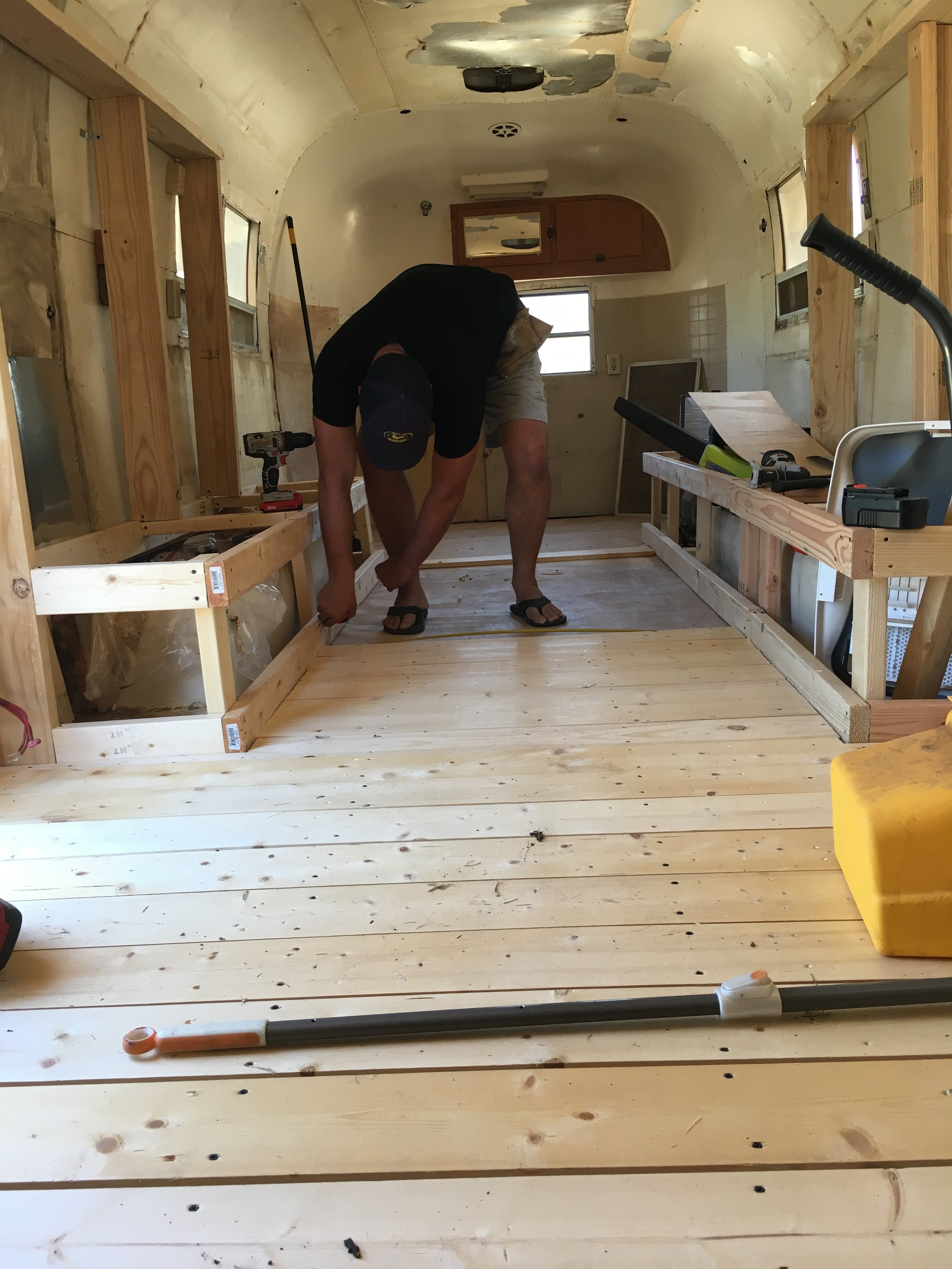 Colin laying the recycled wood flooring in the trailer