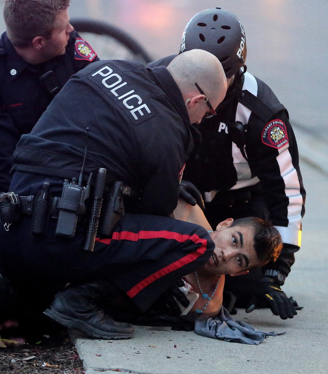 Police try to stabilize a male shot by police by putting pressure on the wound as they wait for medics to arrive after an incident in front of the drop in centre in downtown Calgary on Tuesday, November 3, 2015. This male was a passenger in a stolen vehicle that attempted to run over medics and police officers at an accident scene they had caused moments earlier. Police opened fire on the truck wounding this individual. A female, who was also in the vehicle was arrested with this male after the driver dumped the truck and ran a few blocks away. The driver of the vehicle fled on foot and was still at large.