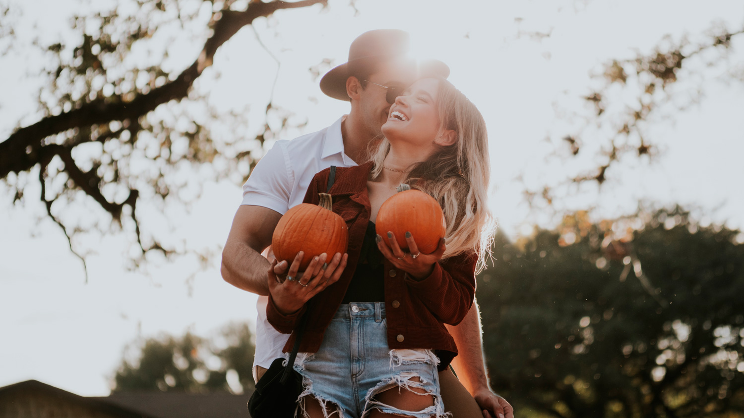 Model couple laughing in a pumpkin patch.jpg
