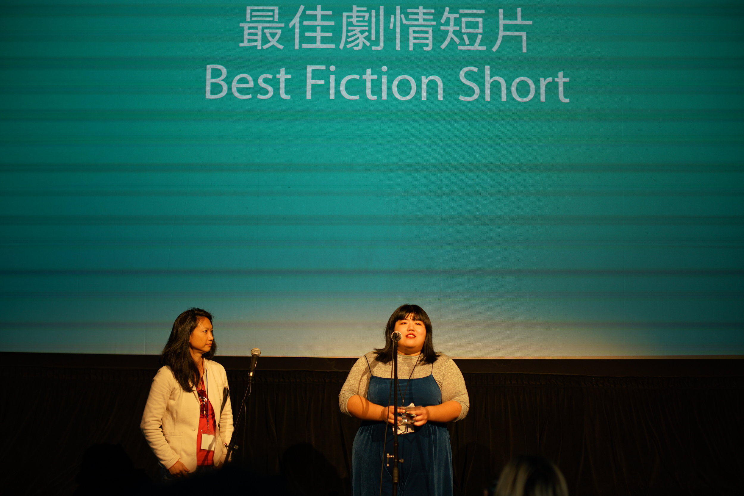 Jury Monica Chuo presents the Best Fiction Short Award (left) programmer Ariel Jiayi Du reads a message from Zuxiang Zhao, director of  A Test  (right)