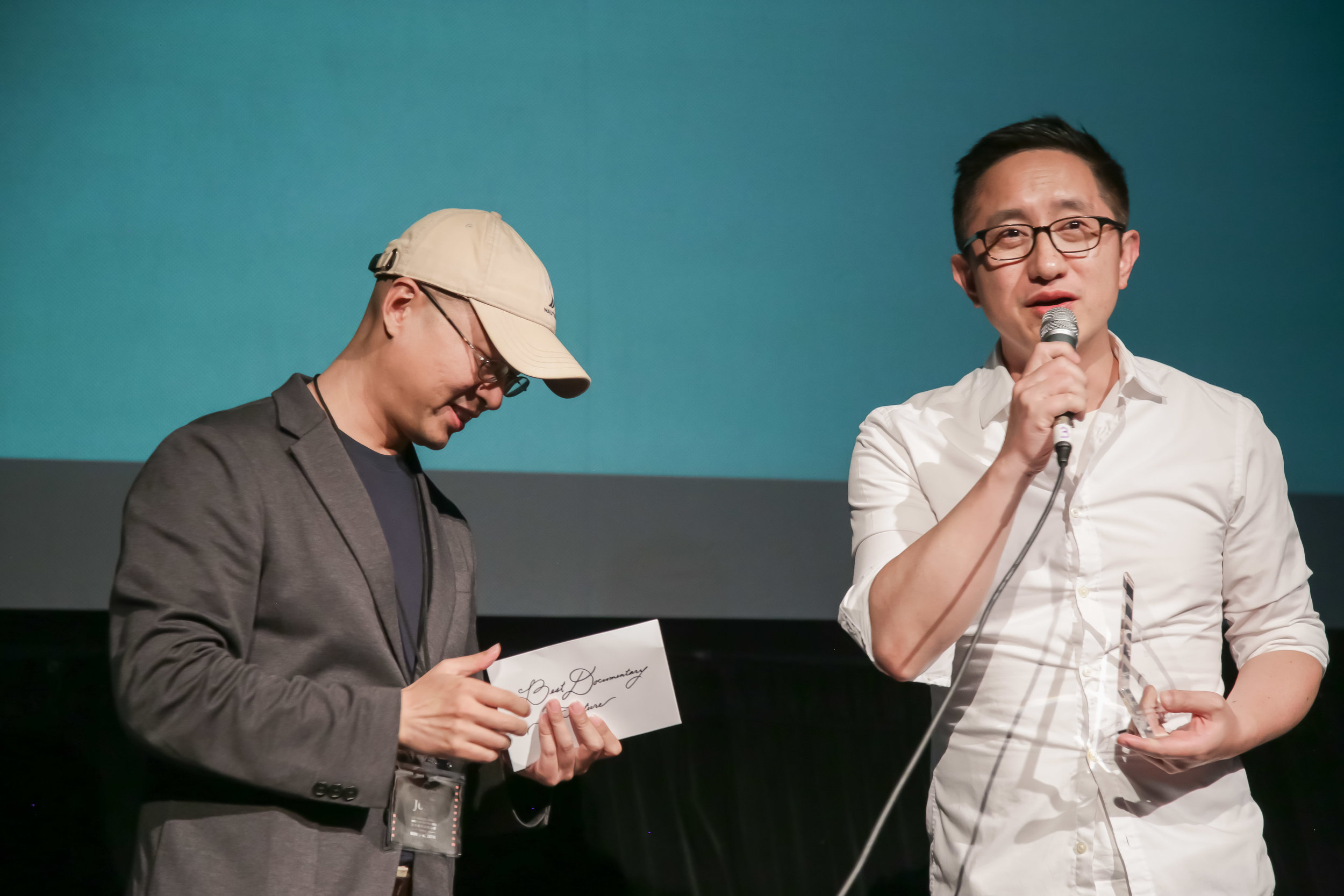 Jury member Richard Liang (Weichao Liang) (left) presents the Best Non-Fiction Feature Award to winner Hao Wu (right).