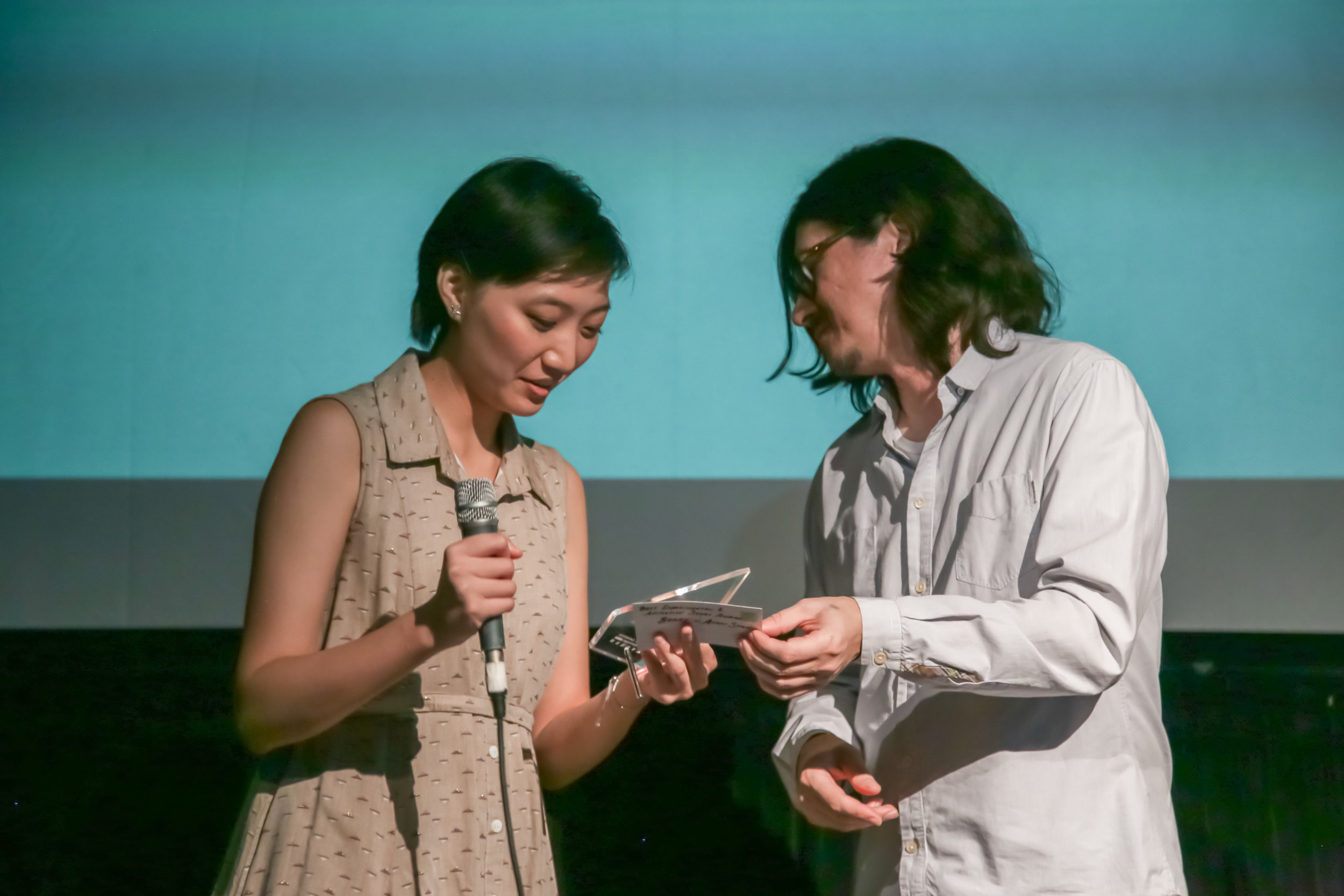 Jury member Helder Sun (right) presents the Best Experimental/Animation Short Award to Director Anchi Shen (left).
