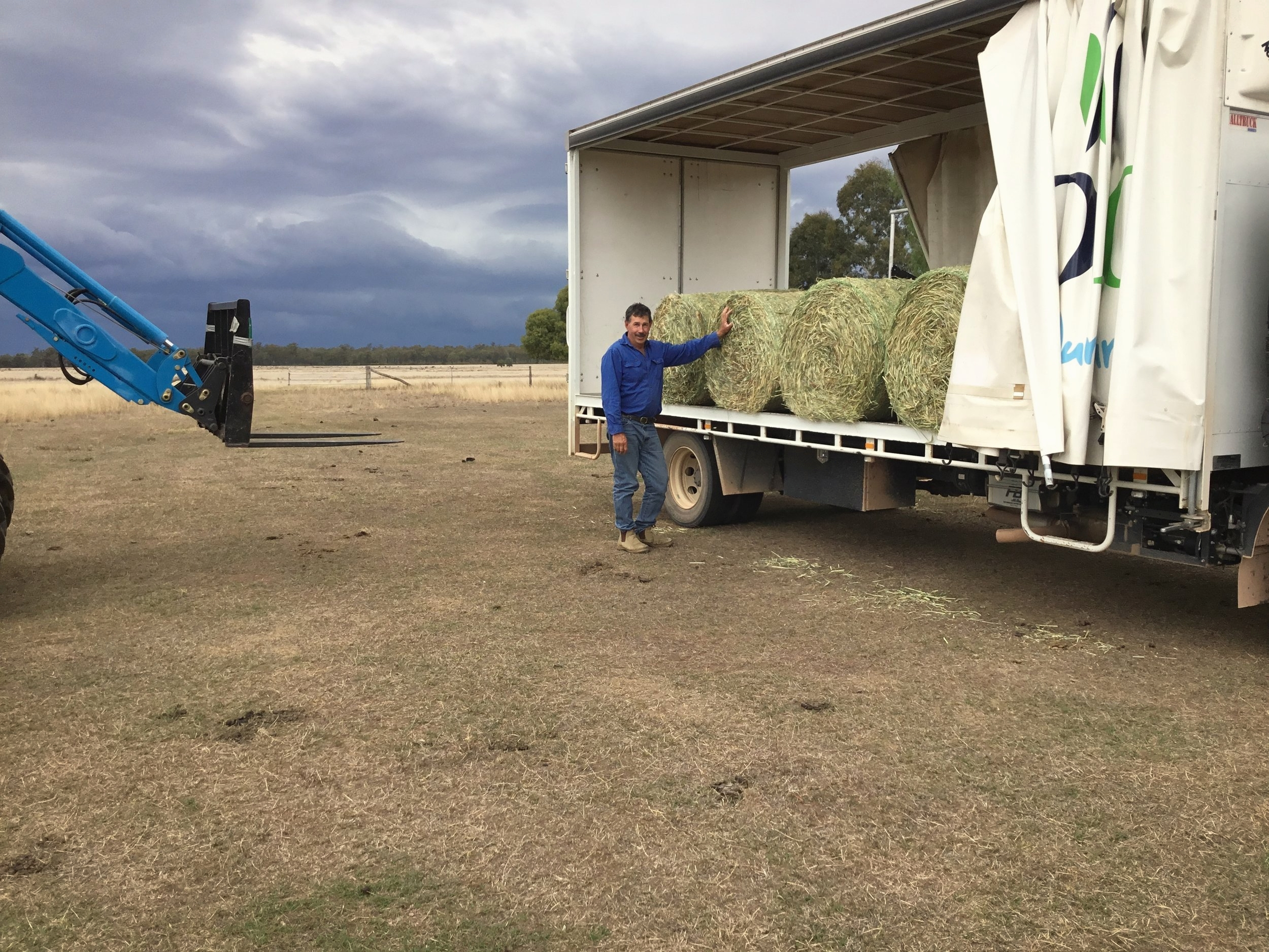 Peter Pohlmann, owner and operator of Bloomfield, stands happily with his hay while storm clouds close in.