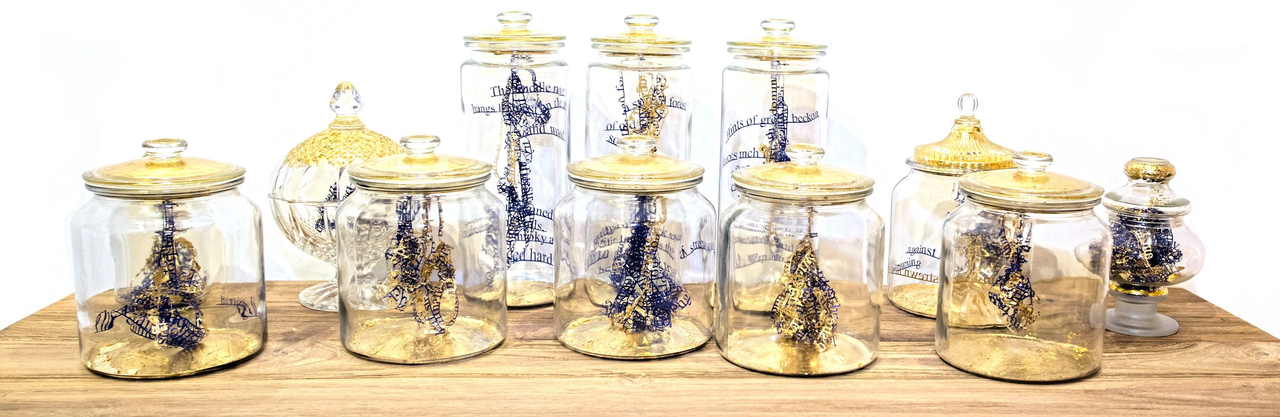 Twelve glass jars sit atop a wooden display piece, all capped with the familiar gold embellishment that seems to be a recurring artwork visual in the exhibition. As you move closer to this wooden table display, you catch a faint but lasting whiff of earthy scents, or Oudh – a delicate fragrance familiar to Kampong Glam.