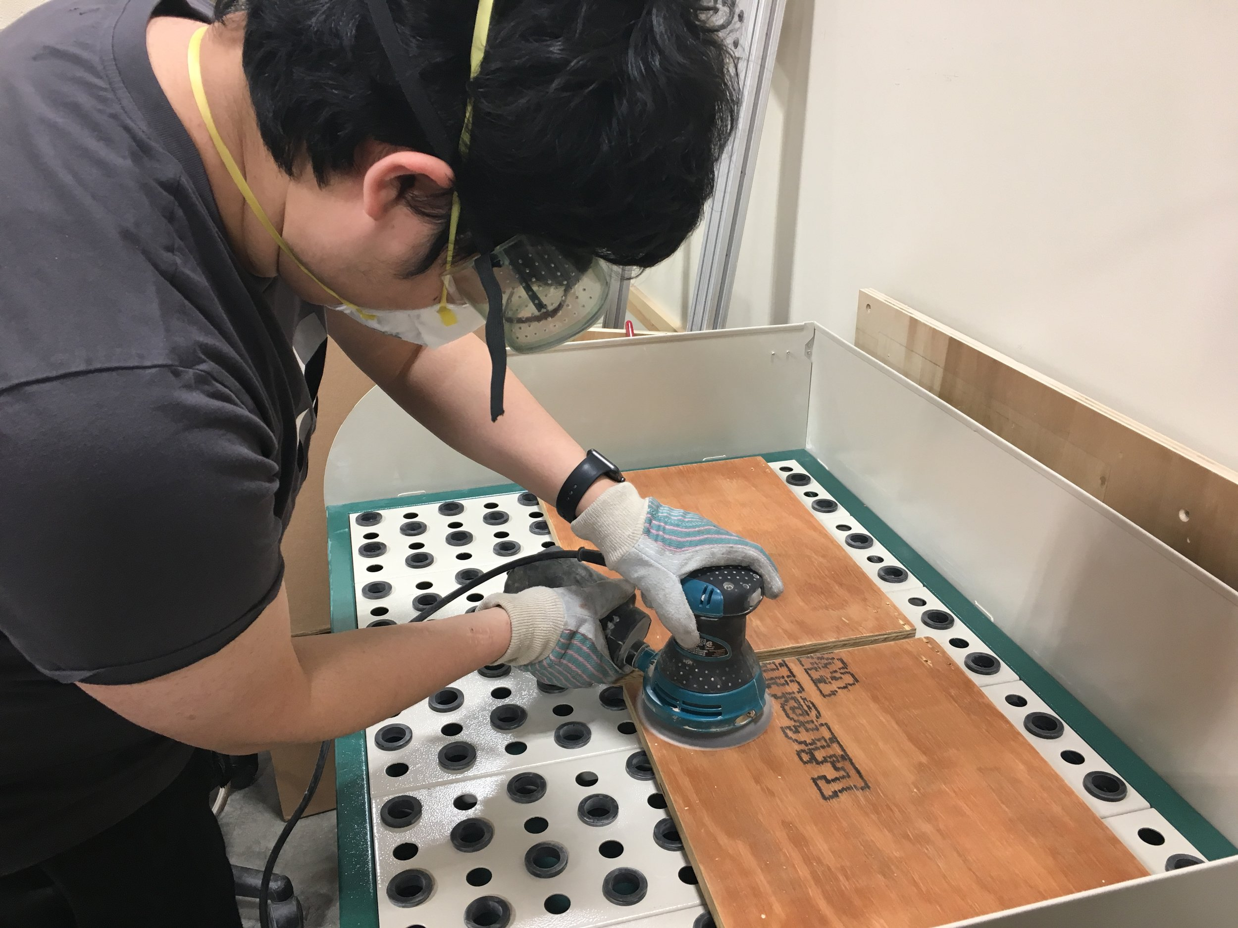 Using an orbital sander to smoothen the marine-grade plywood. (It was really bad plywood feat. Chris Bull)