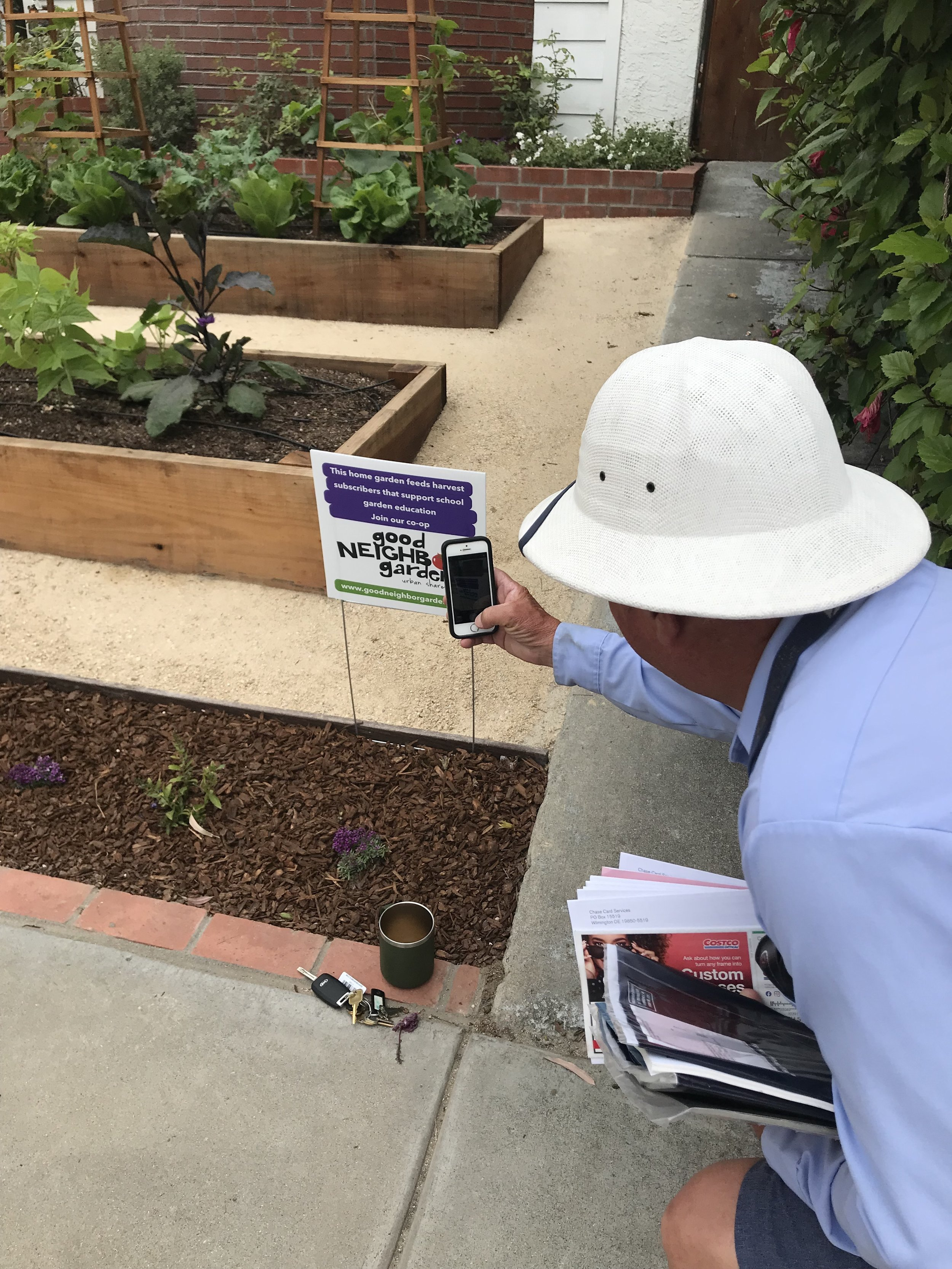 Leonard snaps a photo of the Good Neighbor Gardens yard sign