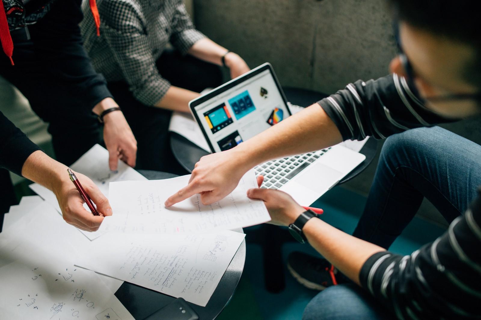 """A group of people brainstorming over a laptop and sheets of paper"" by  Štefan Štefančík  on  Unsplash"