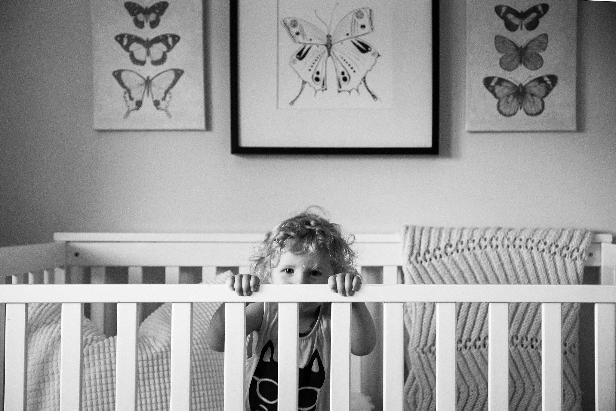 Toddler playing in her crib