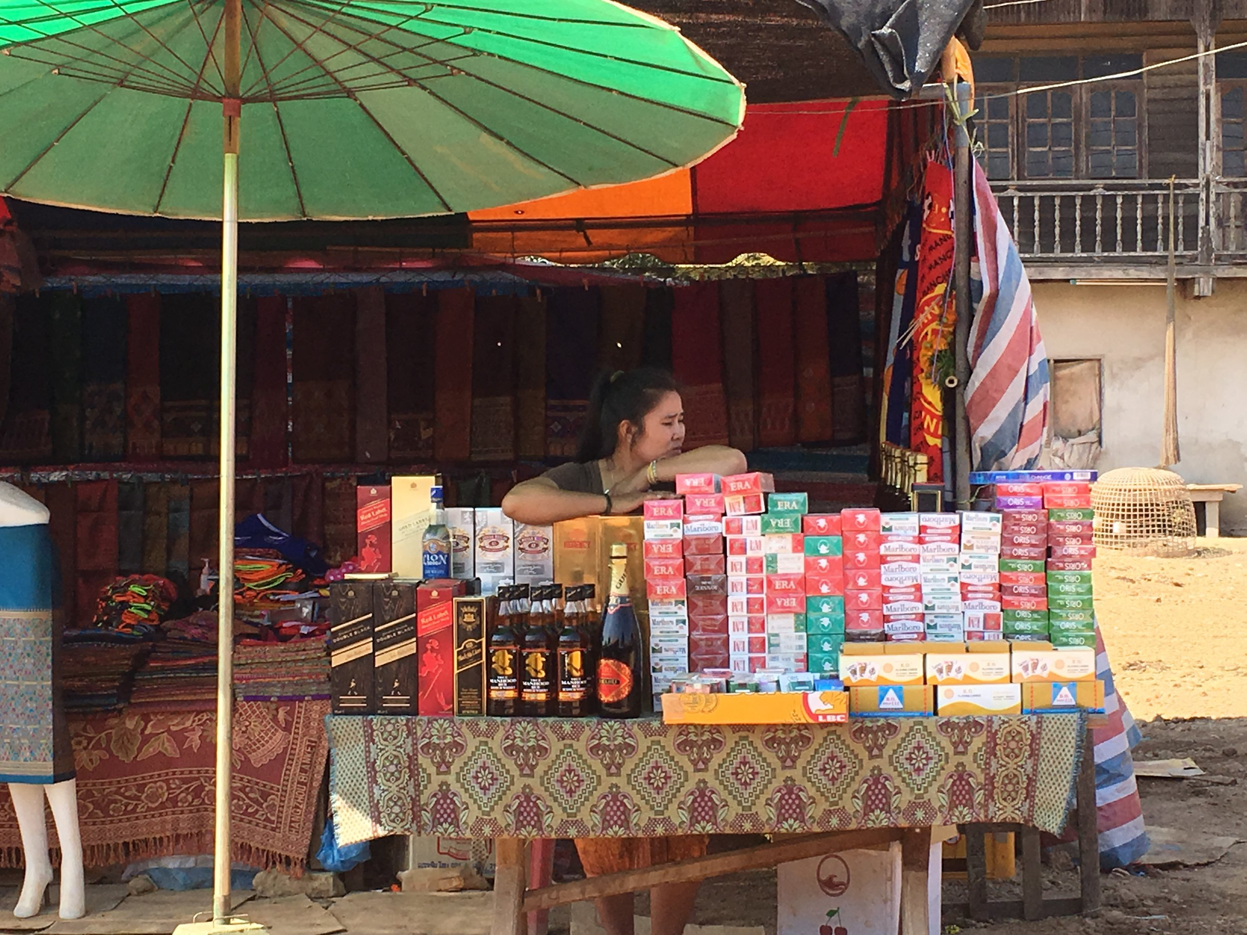 A woman selling liquor and cigarettes in Laos