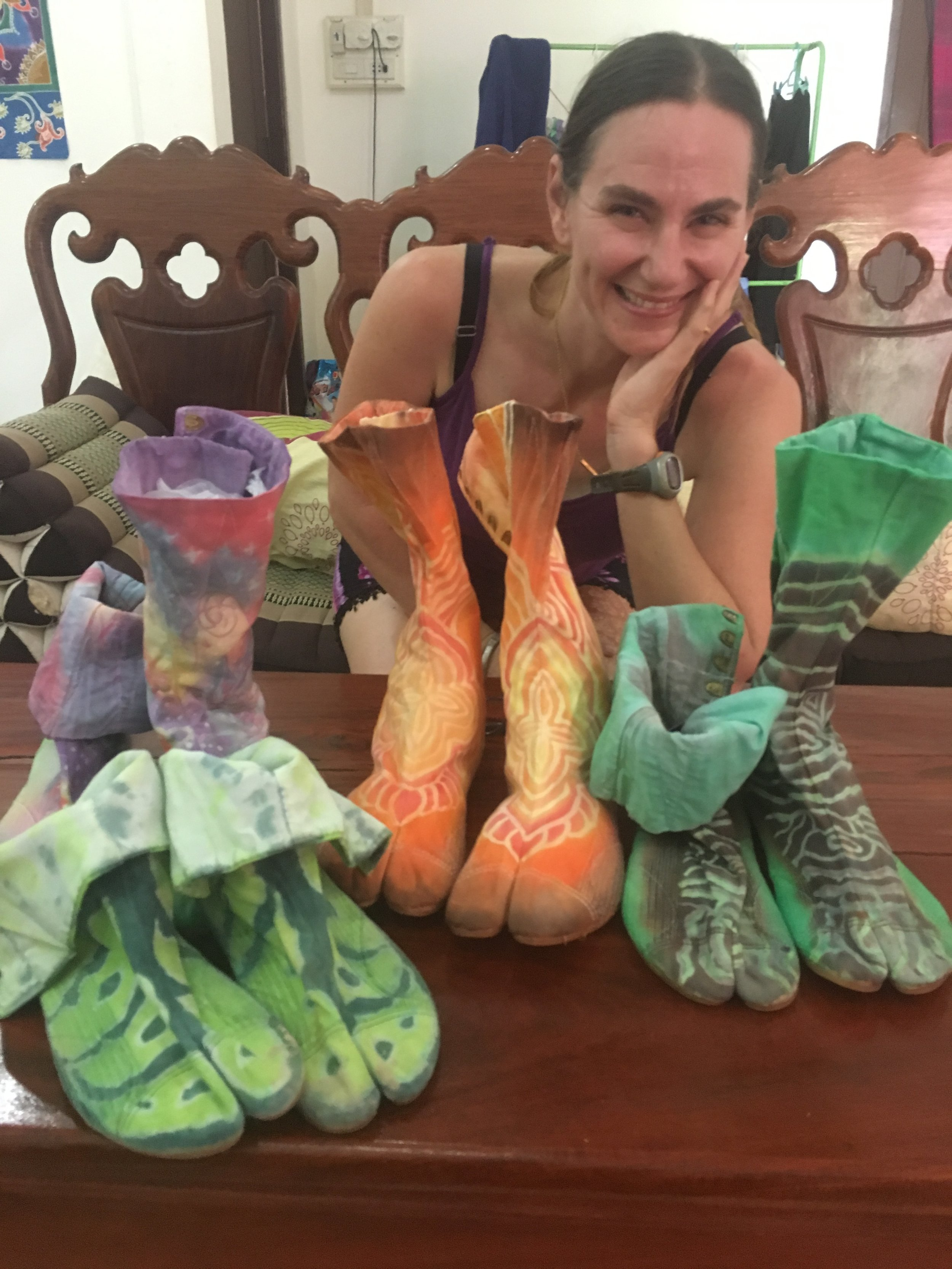 Innana poses with some of the booties she's made in her home studio in Laos.
