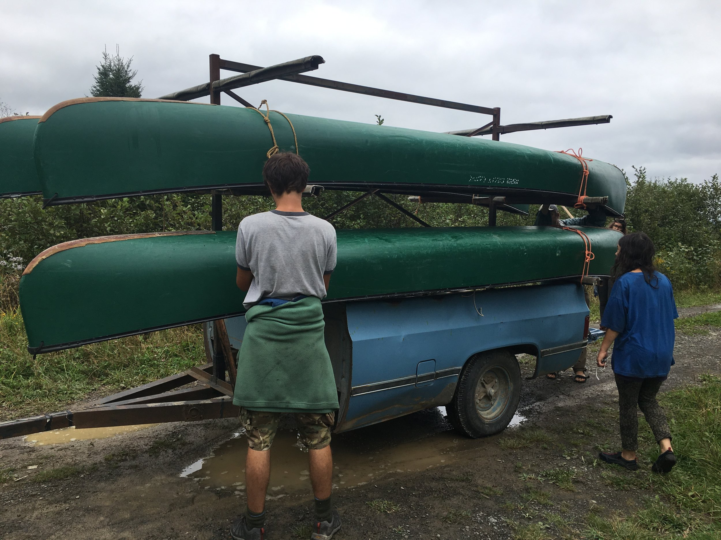 Zander ties down the canoes onto the trailer.