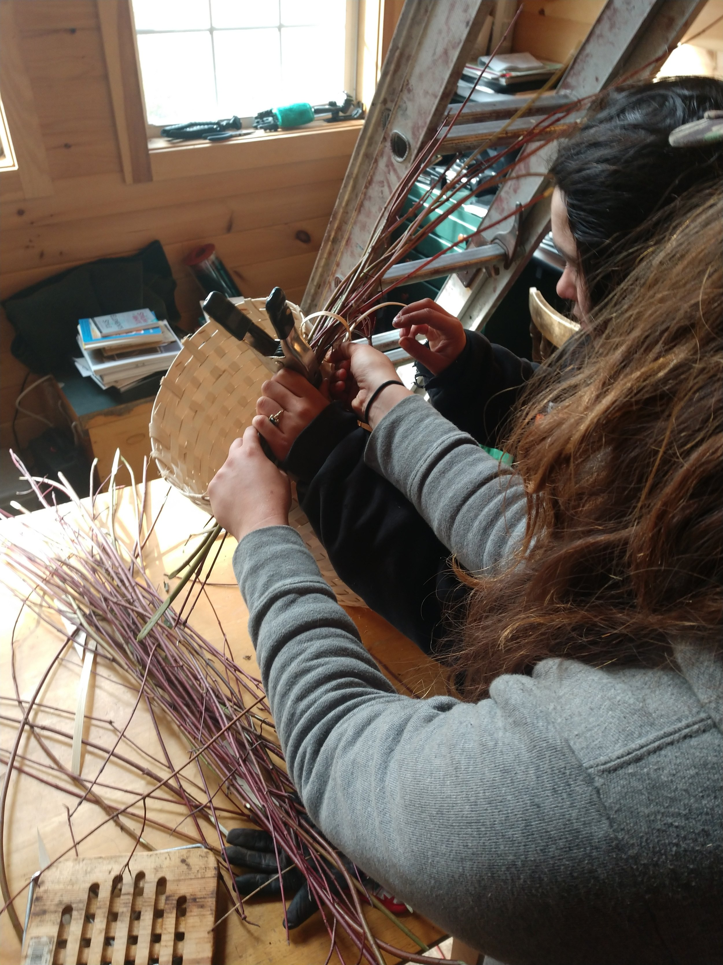 Allison and Molly work on weaving a pack basket.