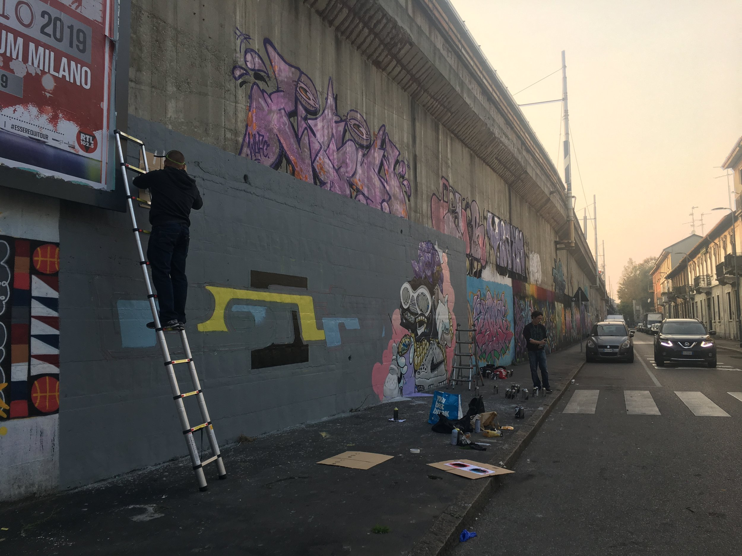 Artists paint on the wall of fame in Milan.
