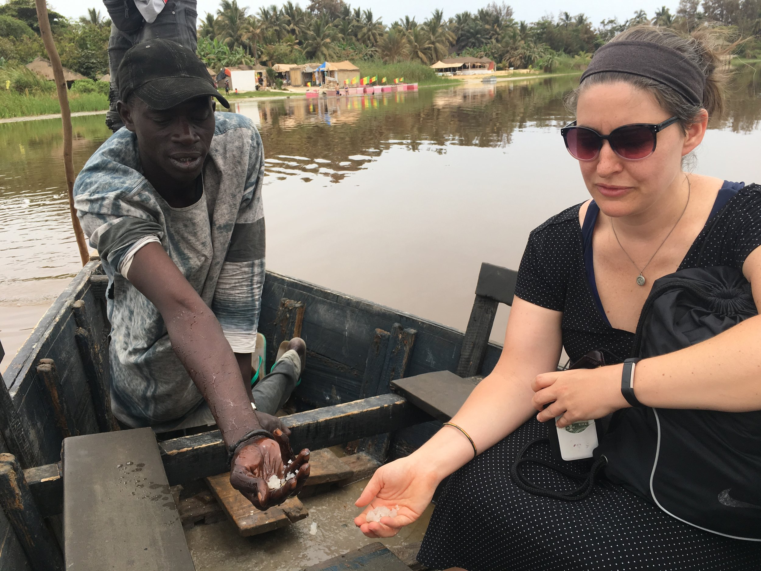 Megan and Lamine hold the salt Lamine scooped off the bottom of the late. The water feels oily and slick.