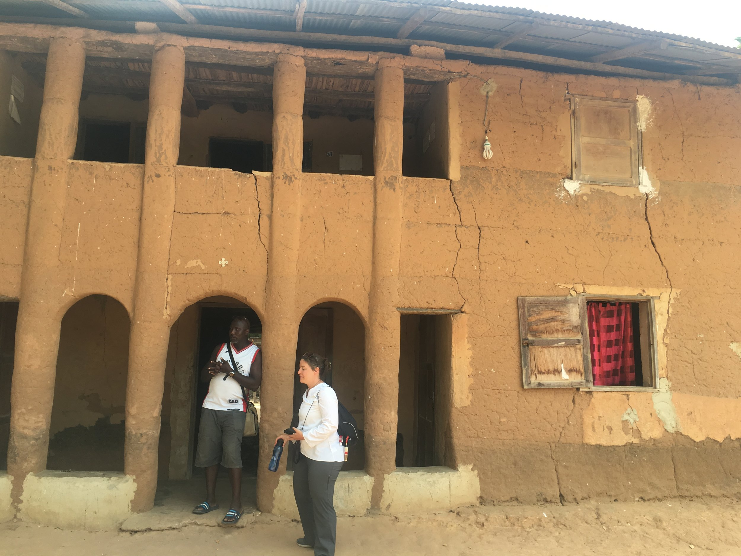 Paco and Megan stand outside the two-story earth house in Casamance.