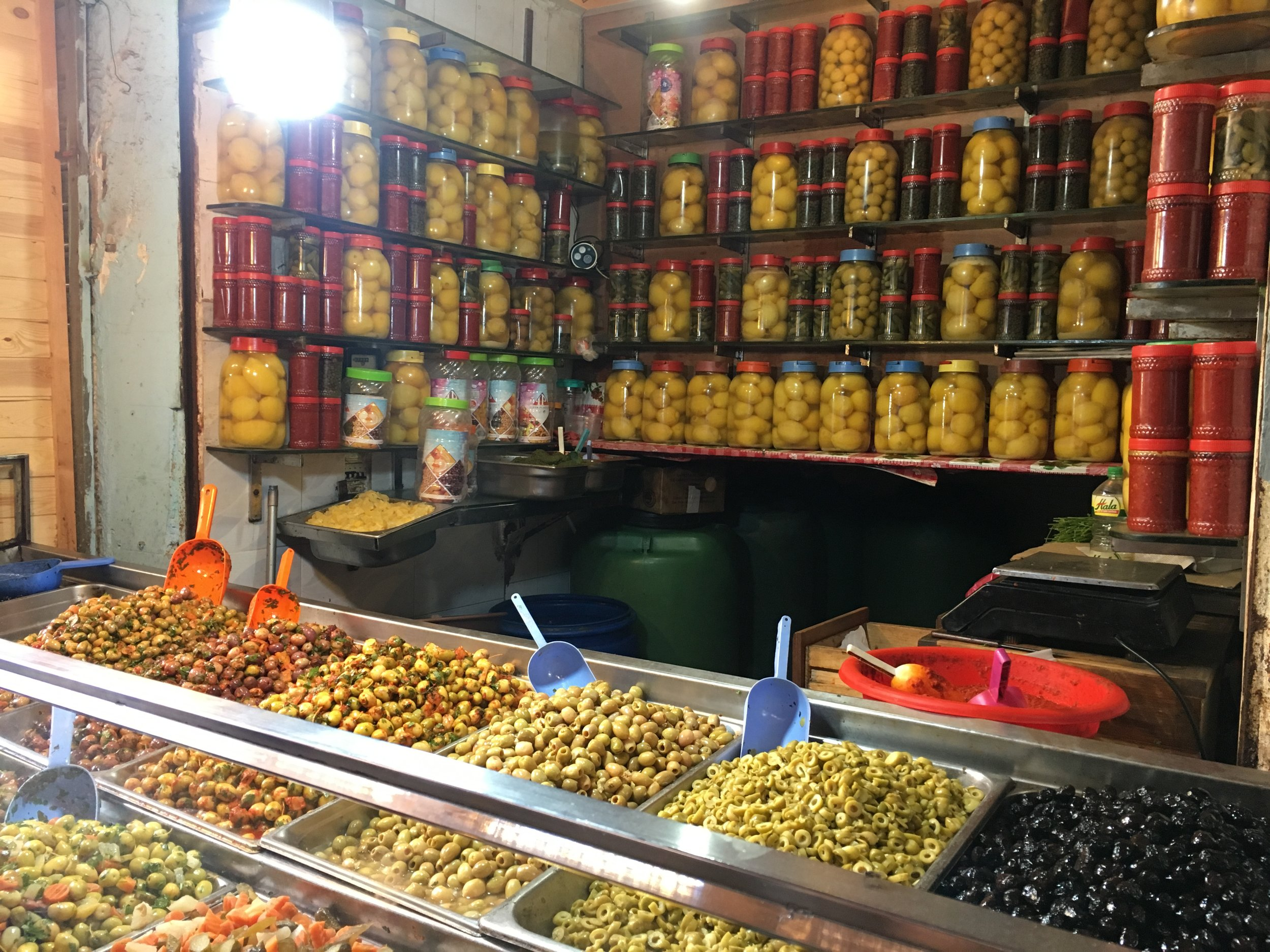 Black olives are simply salted while green (and the purple olives that grow on the same tree) are soaked over and over to lessen their bitterness before flavors like garlic and chili powder is added.