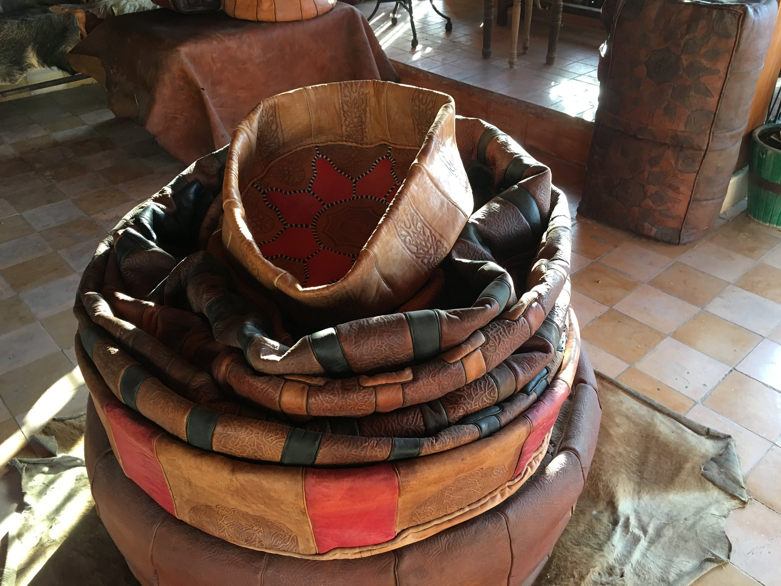 """Hand stitched """"poofs"""" are leather pillow covers of dyed and embossed leather are used to sit on at low tables in many Moroccan restaurants and tea houses. Megan bought one she'll stuff with cotton batting at home then put in her classroom's reading nook."""