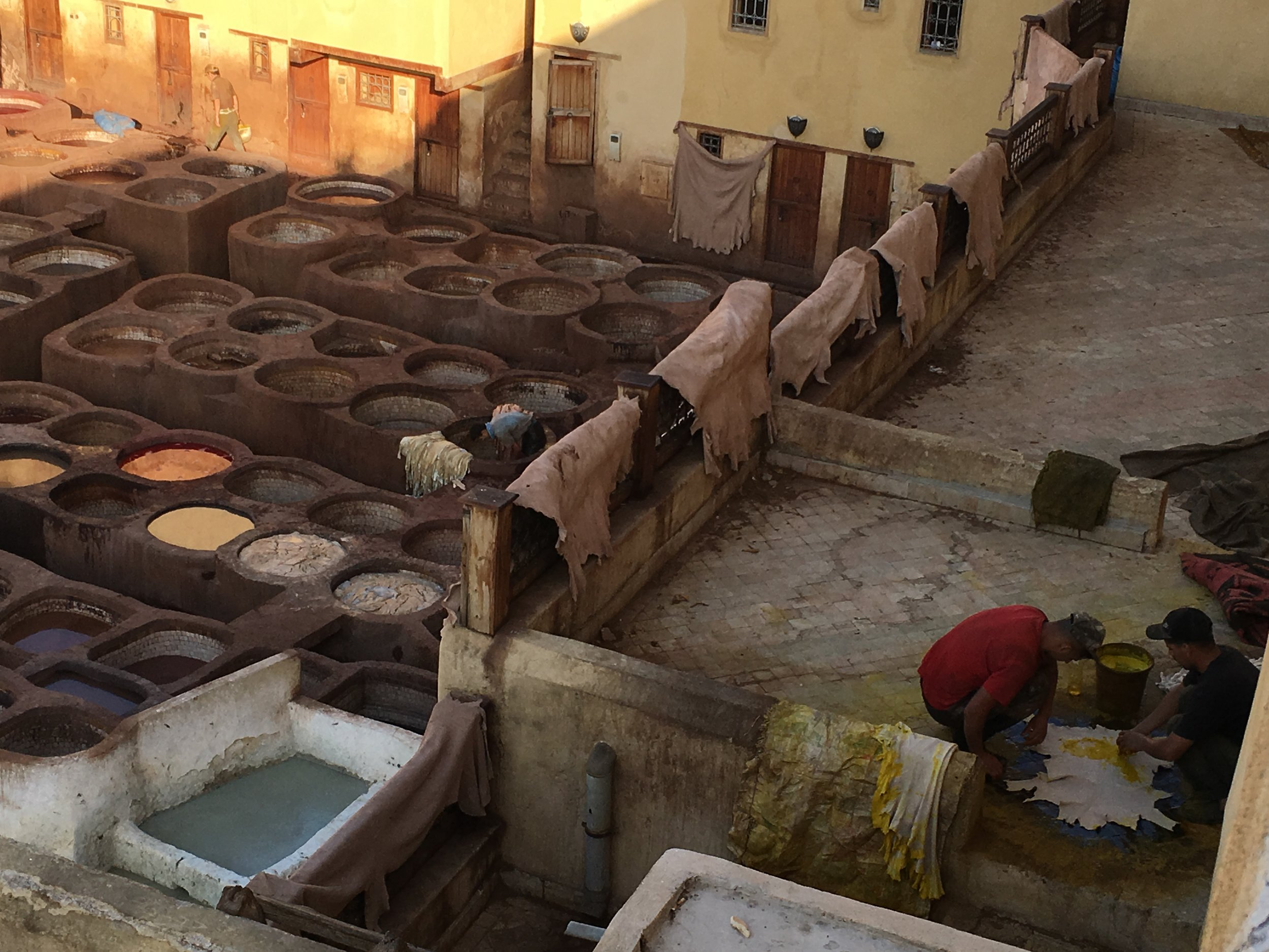 The Chaouwara tanneries use natural dyes. Yellow color comes from Saffron, which is the most expensive and it applied to the hides by hand rather than soaking the hides in vats. Here two men dye goatskins with saffron dye.