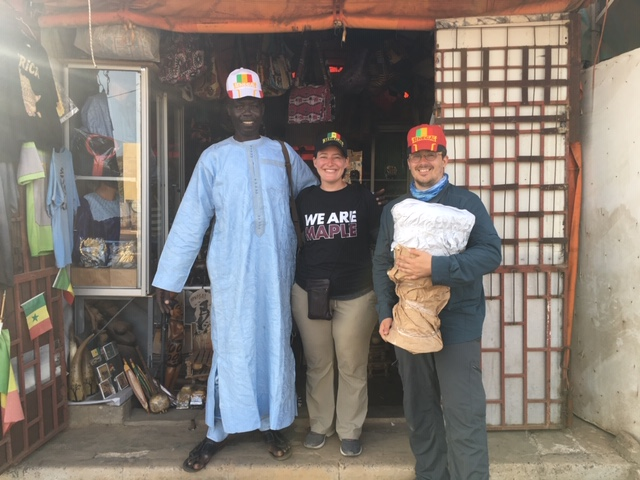 Megan, Chris and the drum salesman wear Senegal caps in Dakar.