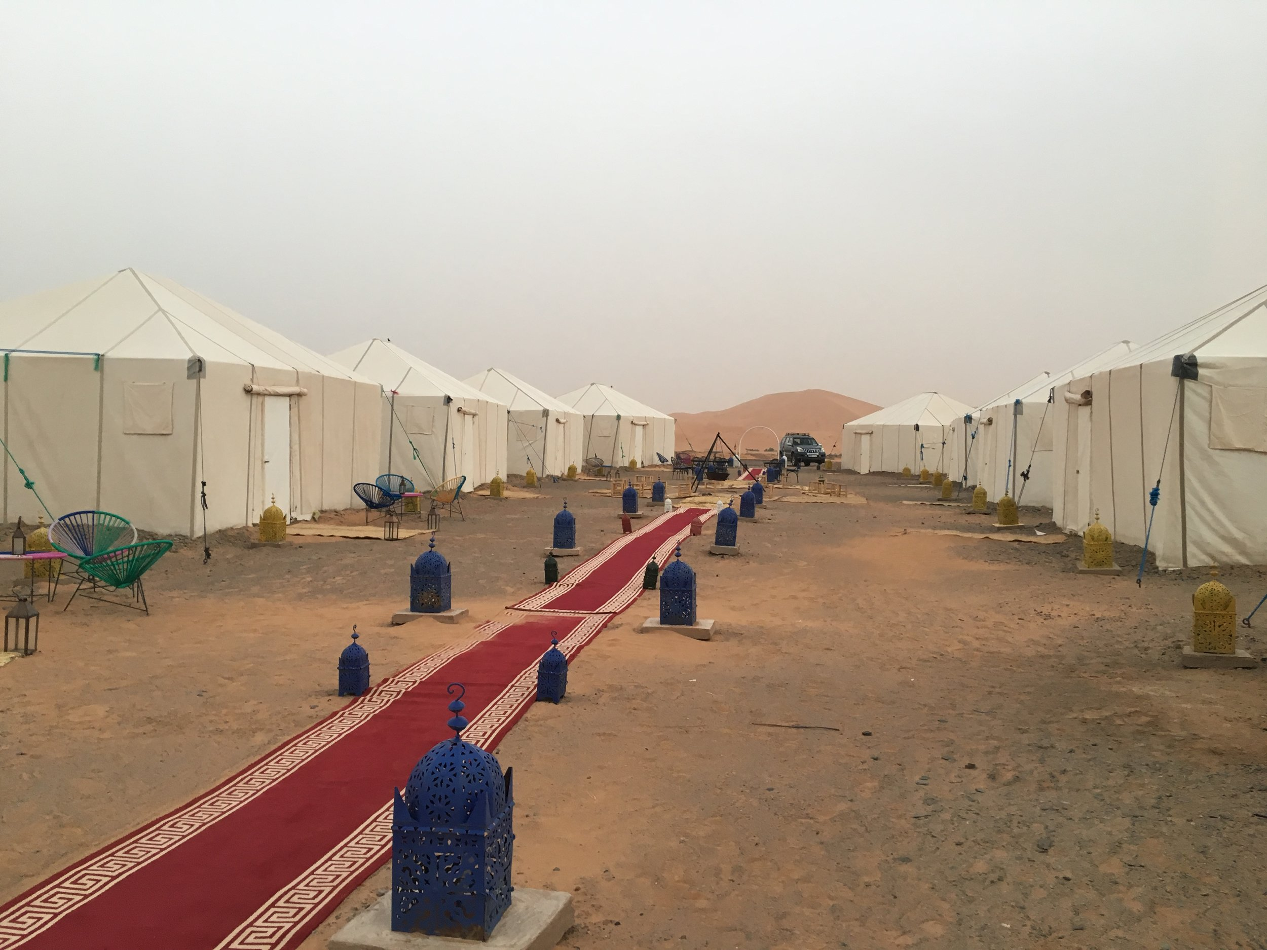 The desert camp in the Erg Chebbii Dunes has 10 tents and a red carpet aisle.