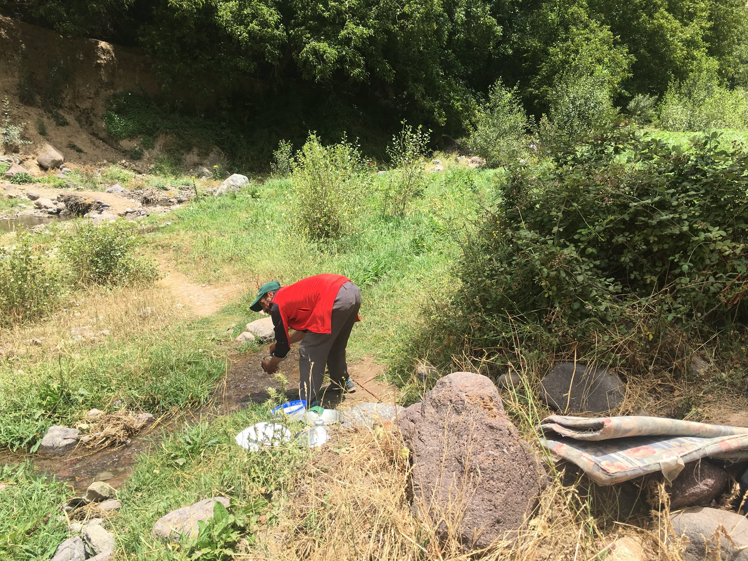 Abdil washes dishes in the river in his signature green baseball cap.