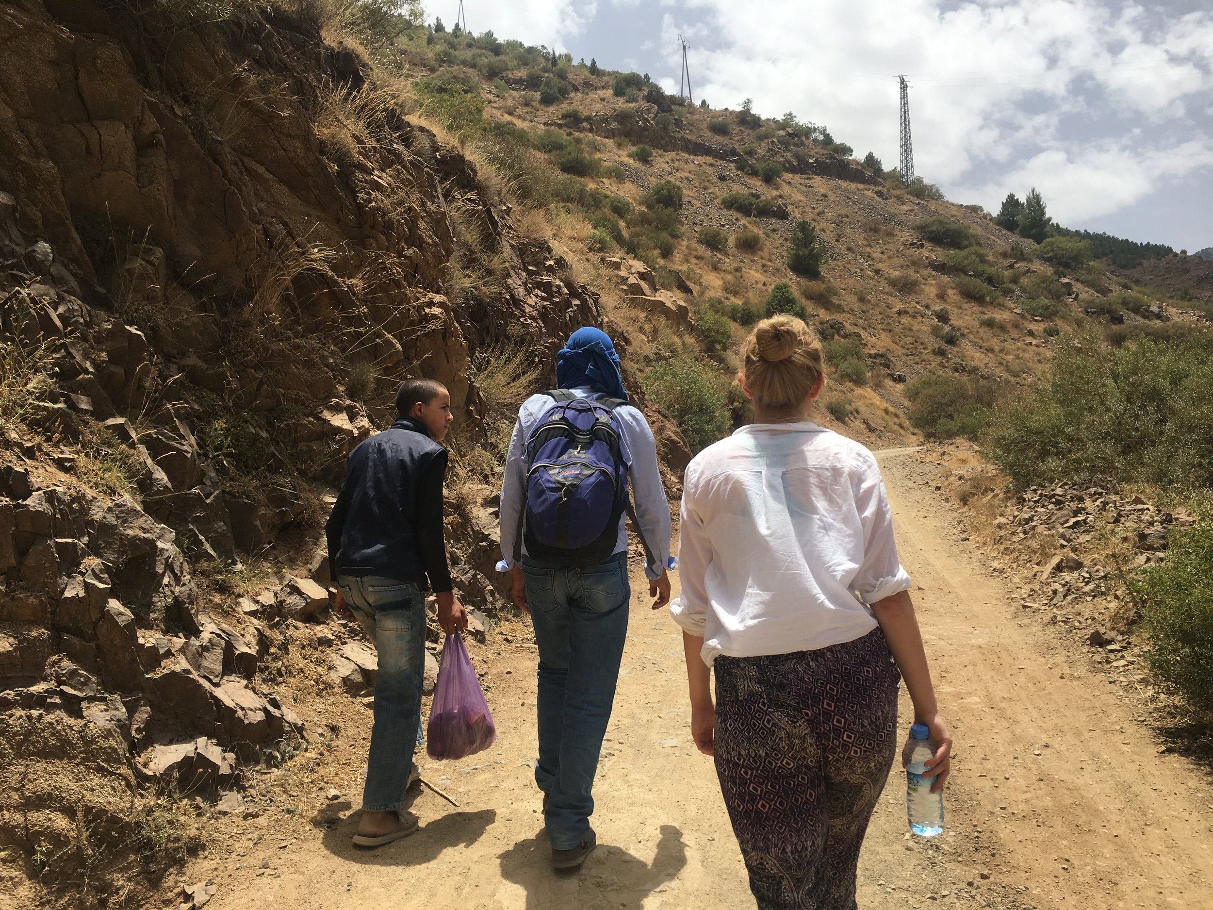 Ali (center) chats with a local (left) as we hike up the mountains.